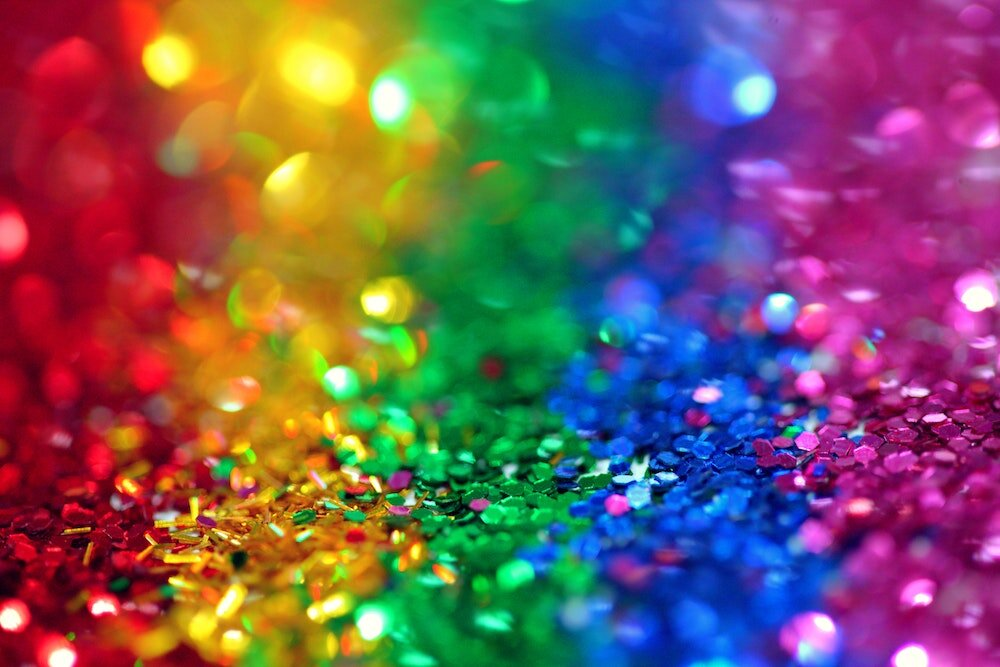 A picture of sequins, arranged in a rainbow