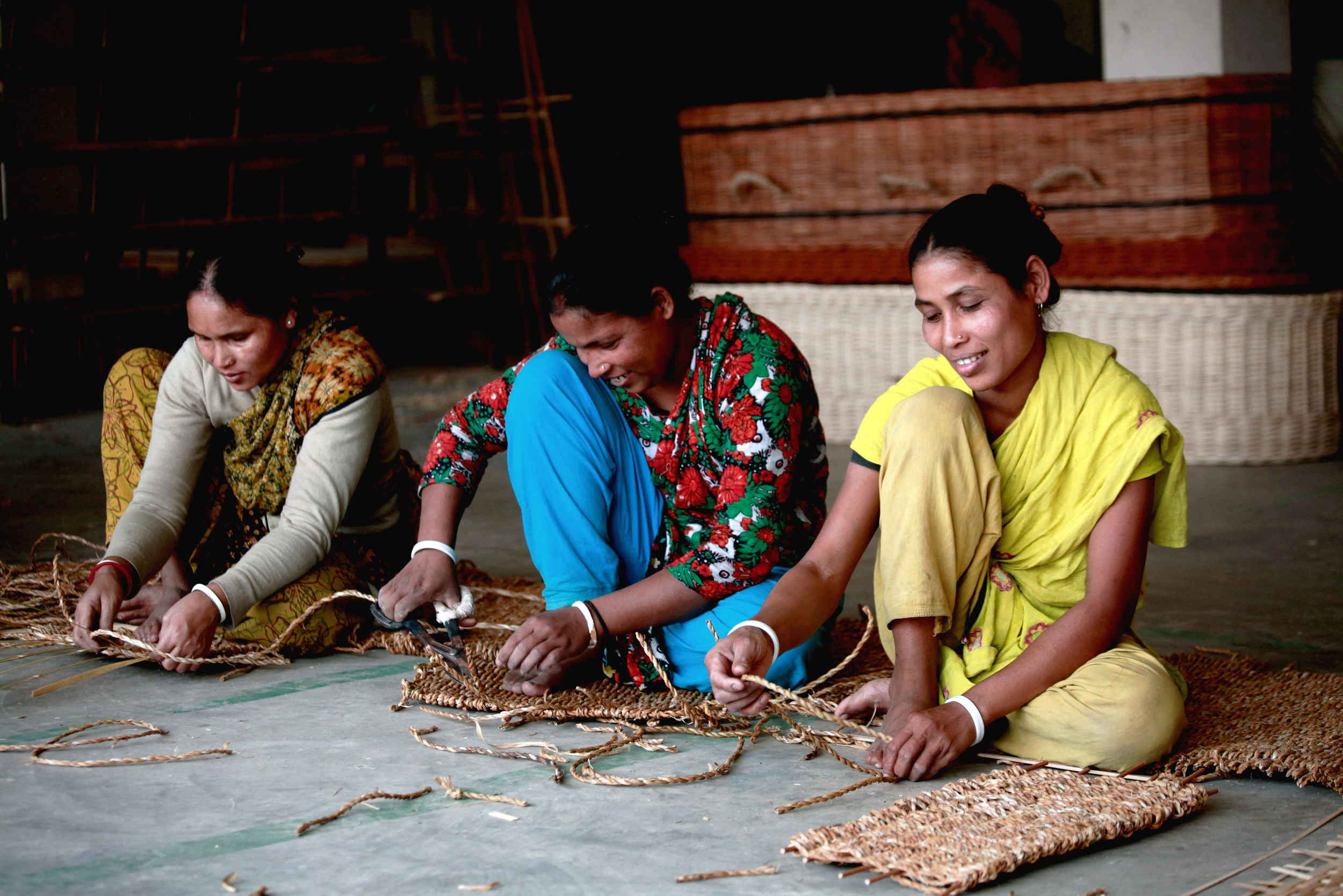 Workers weaving parts of a seagrass coffin