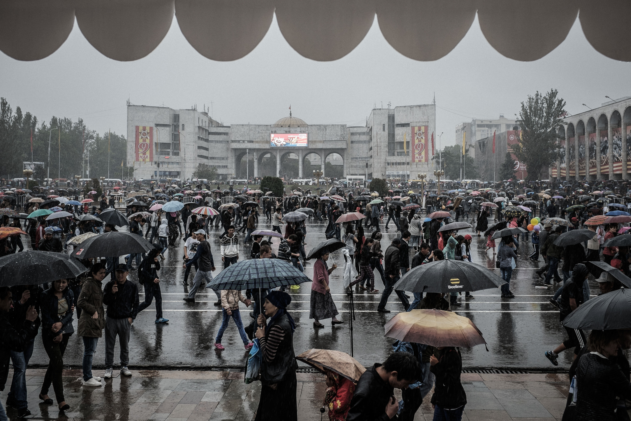 Heavy rainstorm hit Bishkek during the military parade for the 70th anniversary of the Great Victory. Visitors run to get shelter after the end of the event. Ala-too square, Bishkek, May 9, 2015