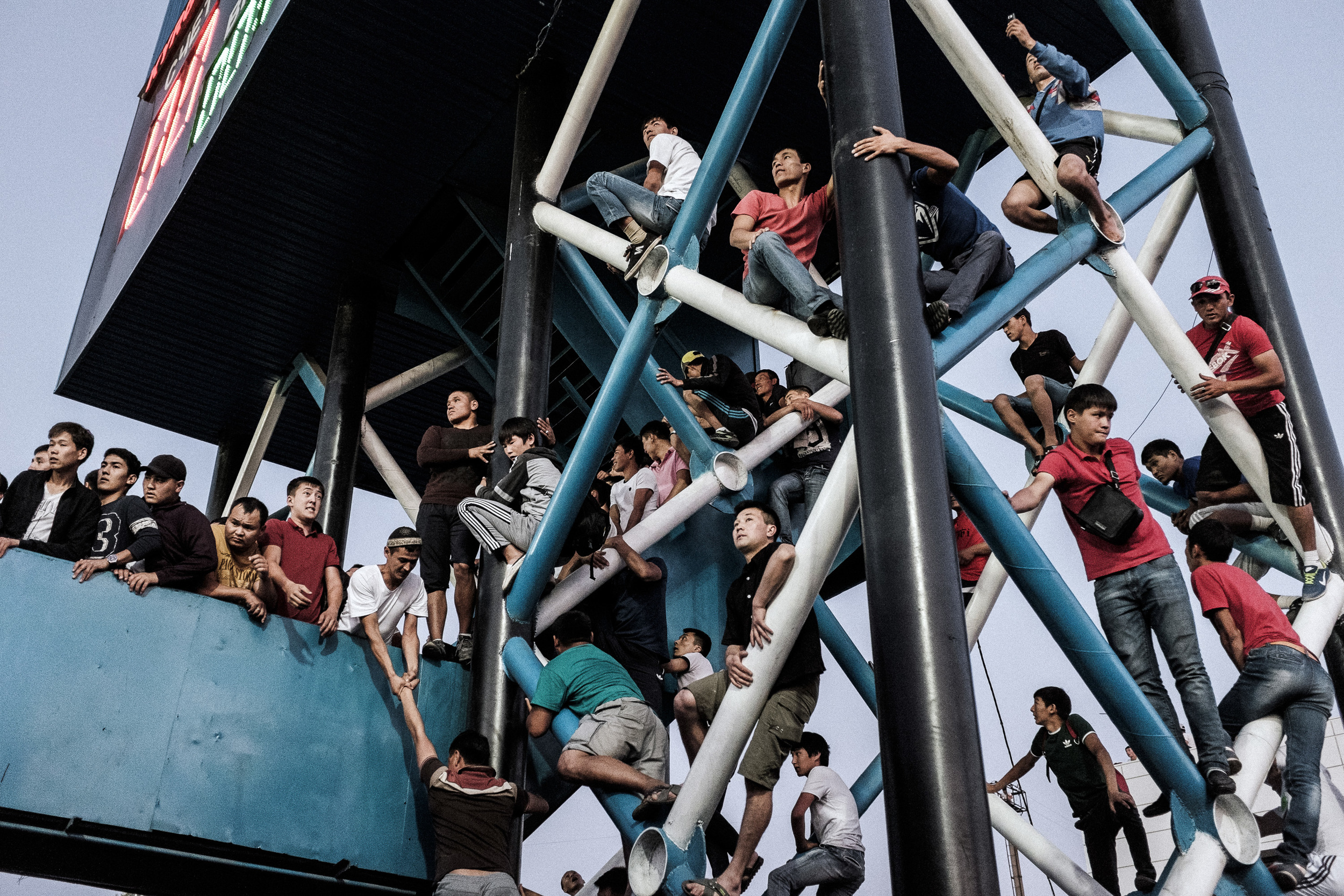 """The outsiders"". Kyrgyzstan - Australia world cup qualifying football game. Kyrgyzstan, Bishkek, 16.6.2015  Some fans perched on light towers, others scaled fences to get in, with an estimated 10,000 more fans crowded outside the gates - including a mob on the rooftop of an adjacent building. The story published on  Global Voices ."