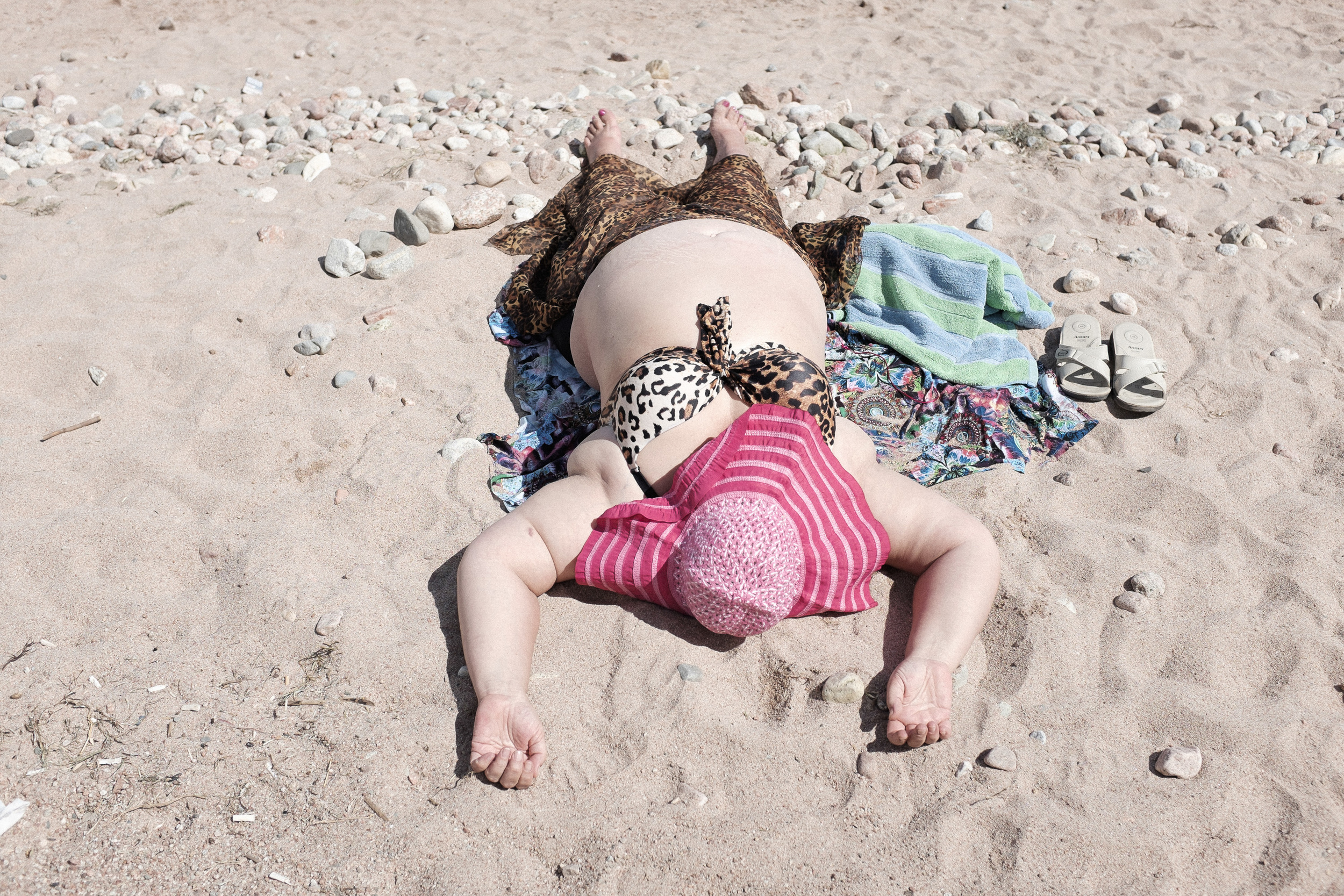 Russian tourist having sunbath. Bosteri village, Issyk-Kul lake.
