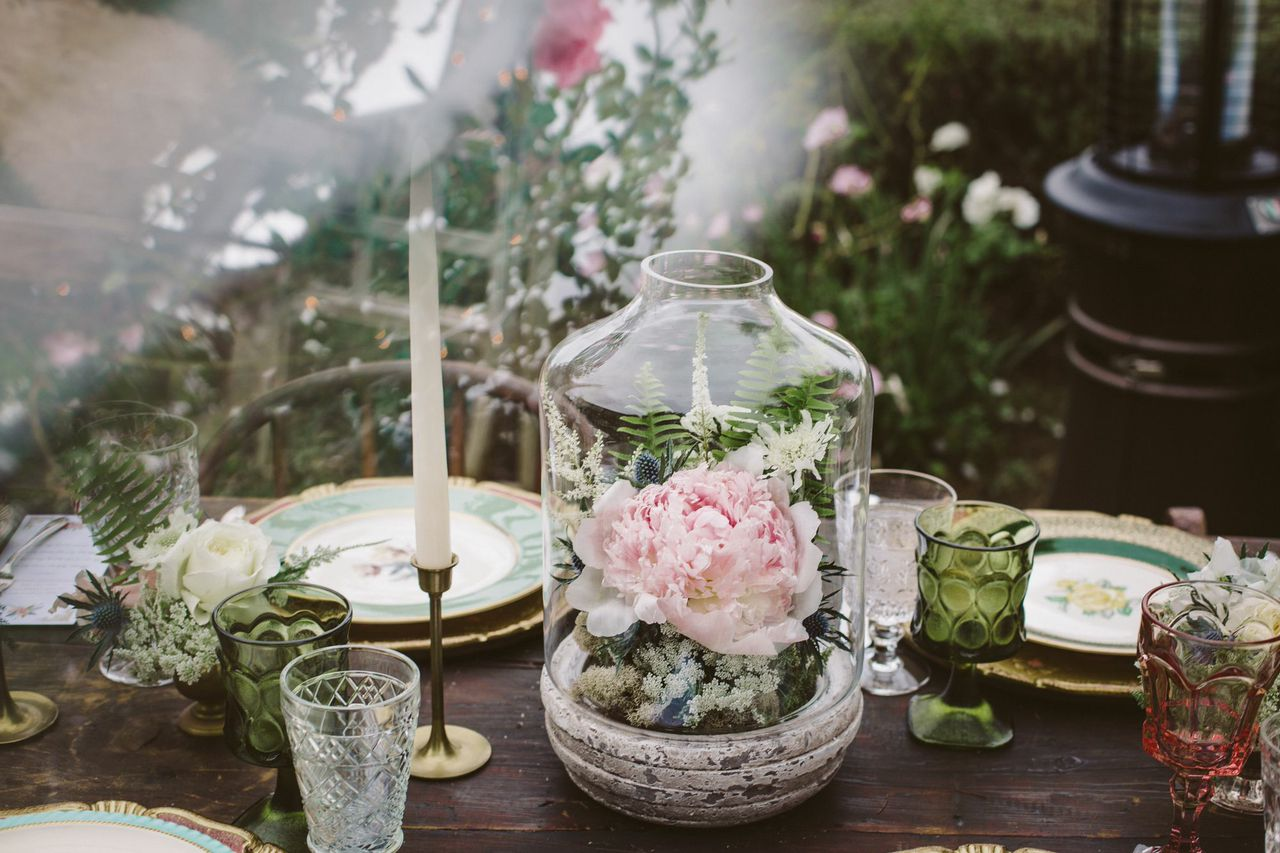 Tip: Glass bell jars were used for the centerpieces, a similar technique as terrariums, but these add a lot more volume and interest. Smaller vases and candlesticks flow down the rectangular tables to elongate the tablescape.