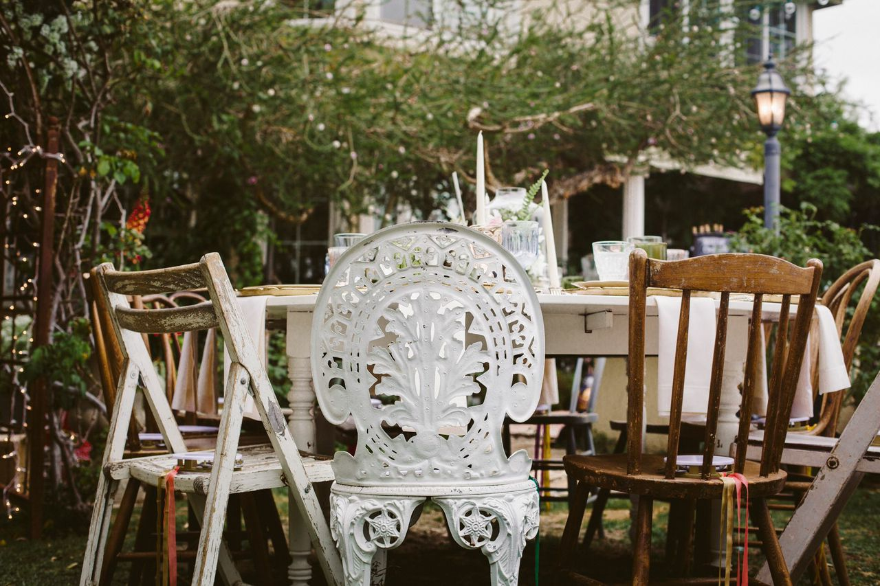 Tip: Mix and match your chairs! I love blending iron chairs with rustic wood ones to break up the usual monotonous row of chairs. Also, we used tambourines as party favors so our guests could sing along with us in our ceremony!