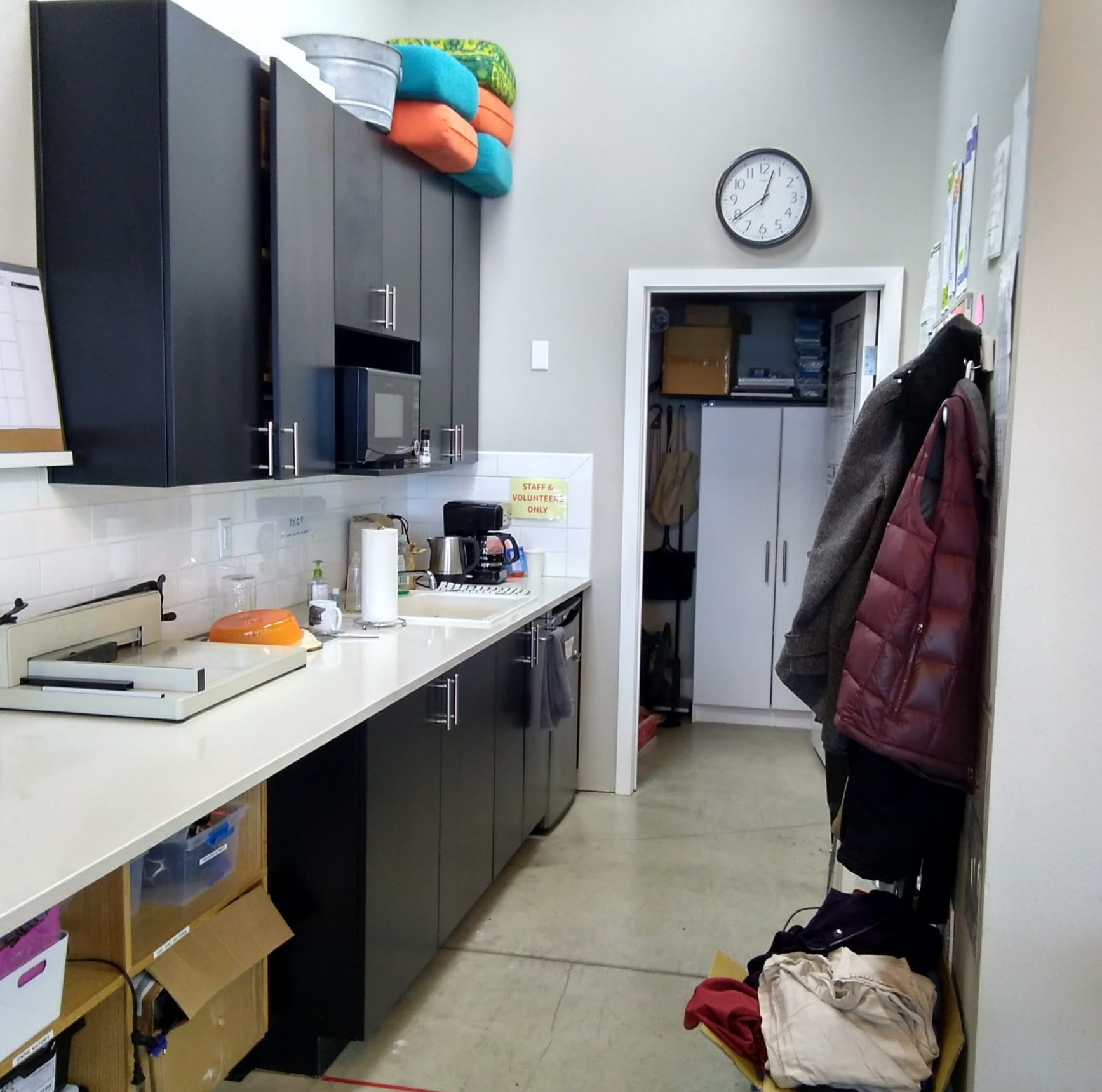 Kitchen - The kitchen area houses a sink, coffee pot, kettle and dishes for staff/volunteer use. Snacks for visitors are stored in the upper cupboards and you will find cleaning supplies below the sink. The wall across from the cupboards holds a bulletin board with volunteer information, time sheets, and pegs to hang your coat/bag.The storage room at the end holds larger items (e.g. Mindstorm Robotics kits) and additional supplies.