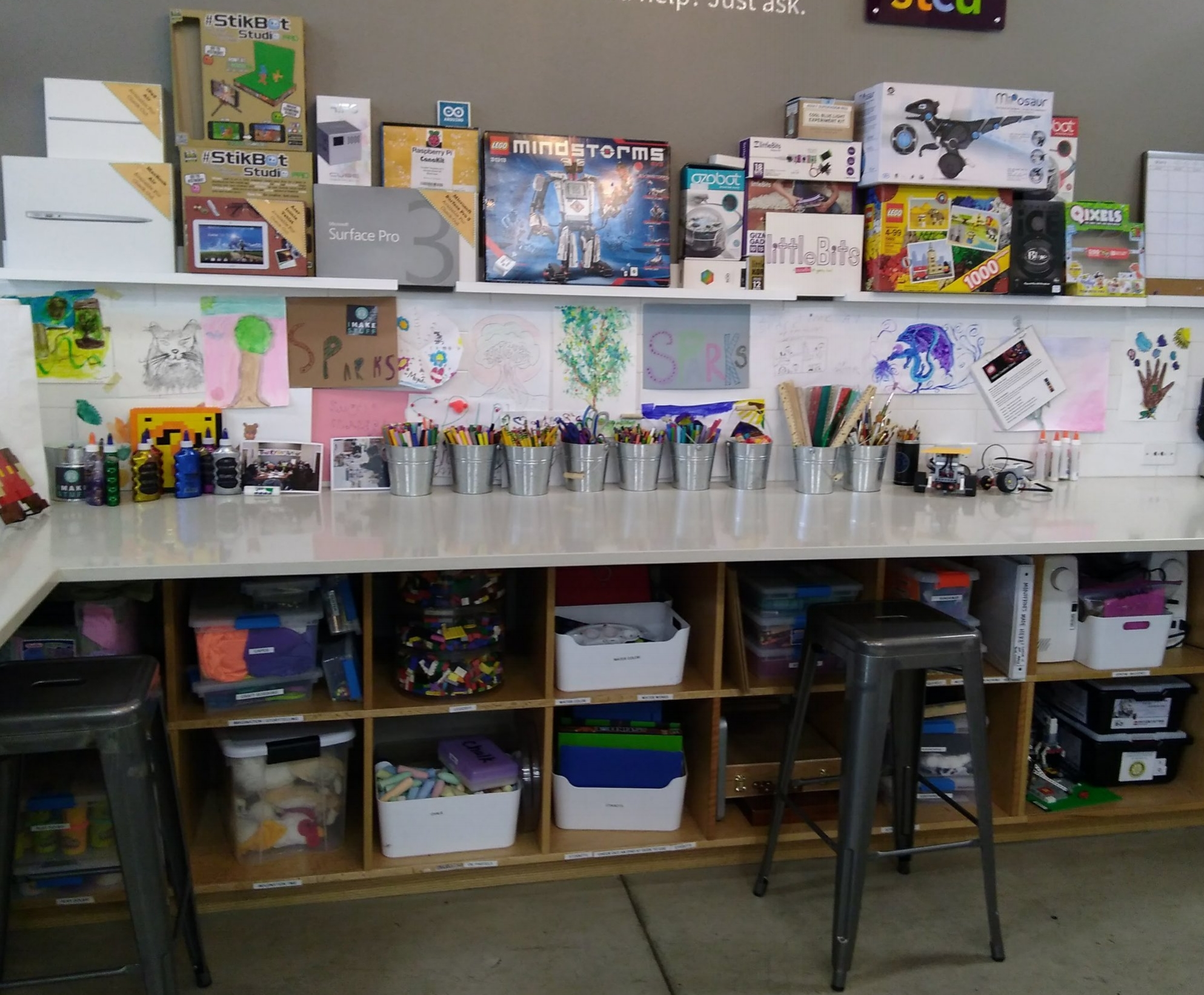 Maker Space - Materials to be found within this space include: art and craft supplies (paper, scissors, fabric, string, tape, glue, markers, pencil crayons, stamps/ink), paper cutter, stapler, paper clips, computer components, chalk, playdough, Lego pieces and various related odds and ends.The Tech Kits displayed in this area are actually stored within the cupboards under the front counter of the Volunteer Station.