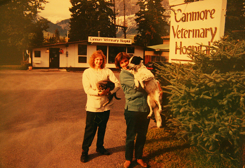 Dr. Karen MacMillan, the clinic cat, Dr. Sylvia McAllister and Hannah in front of the original hospital building in 1990.