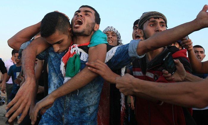 Palestinians carry a wounded protester, during clashes near the Gaza border fence last week. Photograph: Majdi Fathi/NurPhoto/Corbis