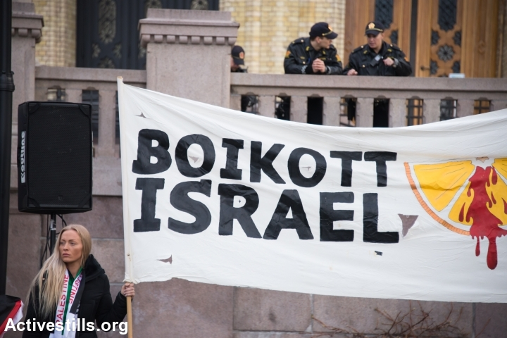 """Police watch from above as solidarity activists hold a banner reading """"Boycott Israel"""" during a protest in front of the Norwegian Parliament building, Stortinget, Oslo, March 30, 2015. (photo: Ryan Rodrick Beiler/Activestills.org)"""