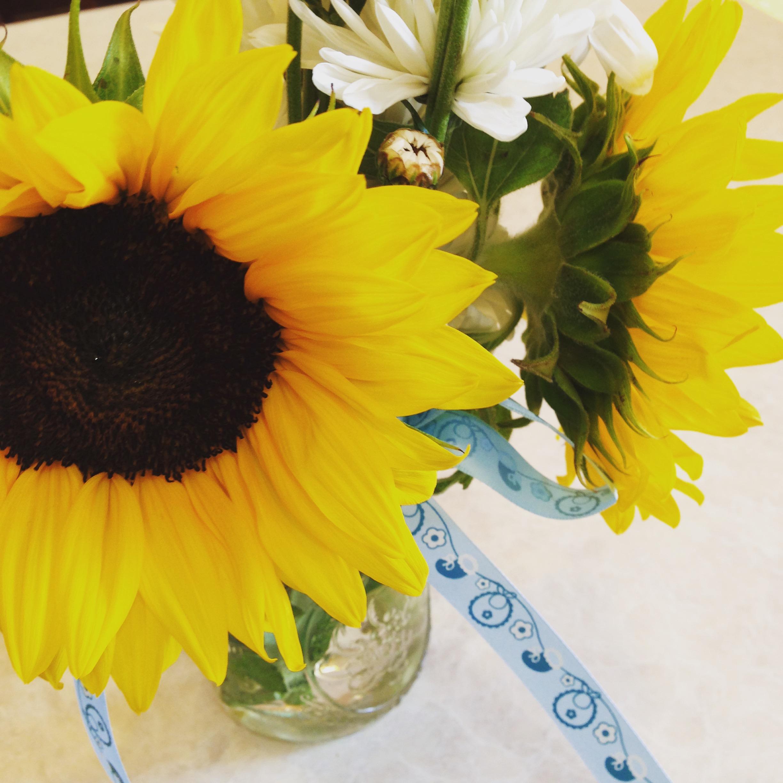 A pretty baby shower flower arrangement in a mason jar.