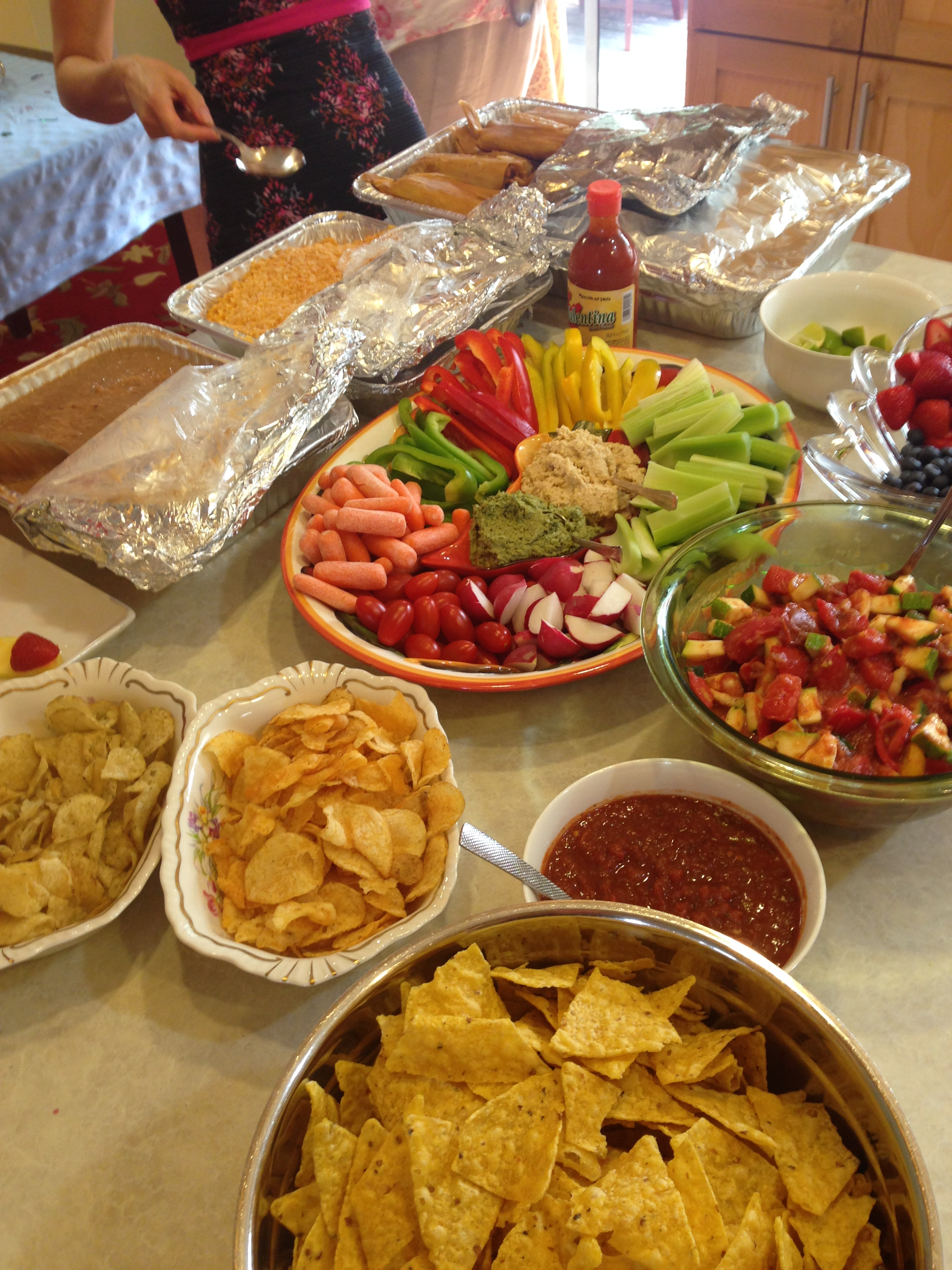 An example of the main elements of a party buffet: a main dish, a veggie platter, fruit platter and chips.