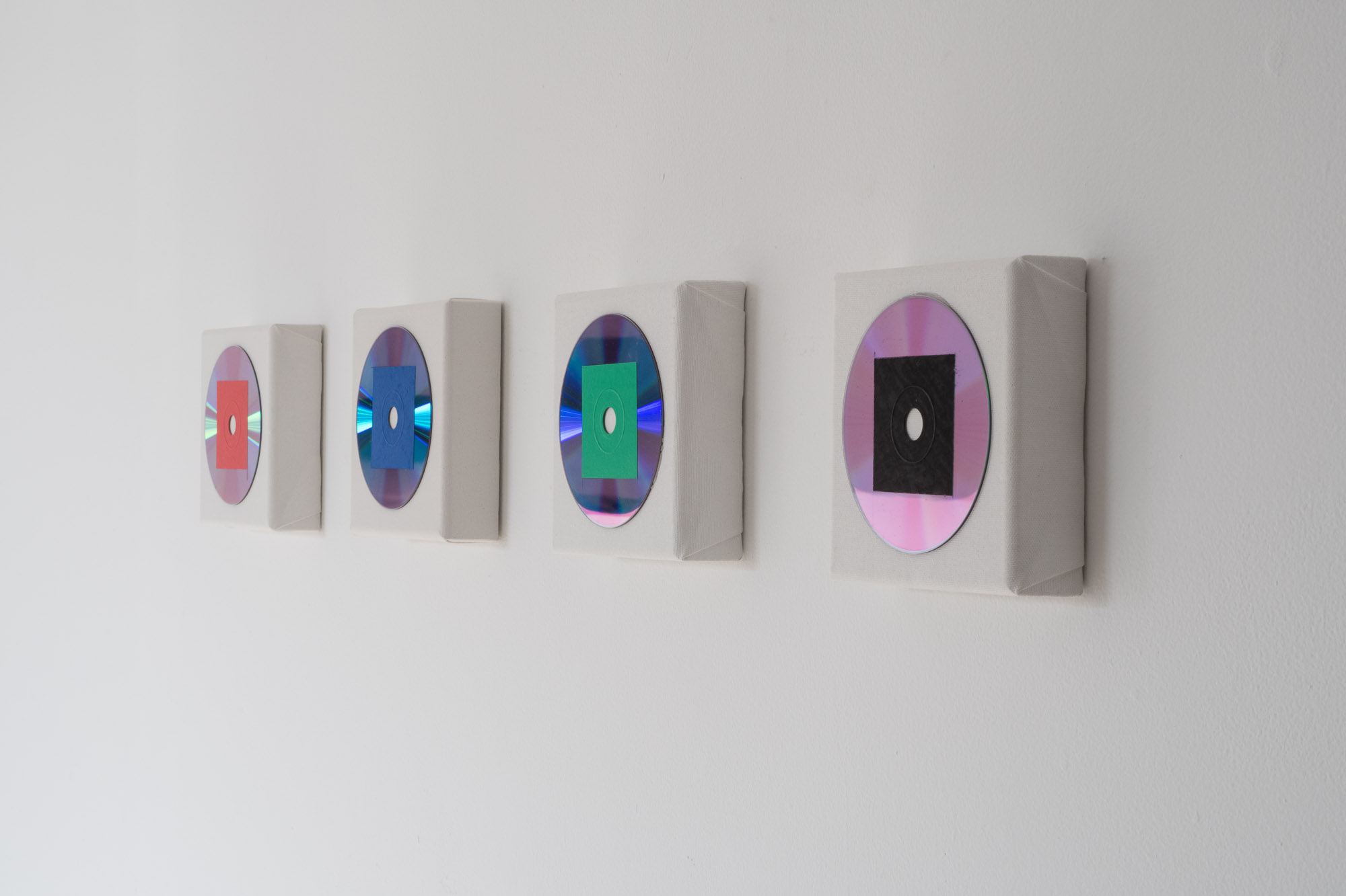 From left to right, Video Works 1 to 4, each work consists of a CD containing my video work, The Real Thing. The CD is coloured with one of the additive primaries and then stuck to a small canvas. To view the video work, the artwork needs to be destroyed.
