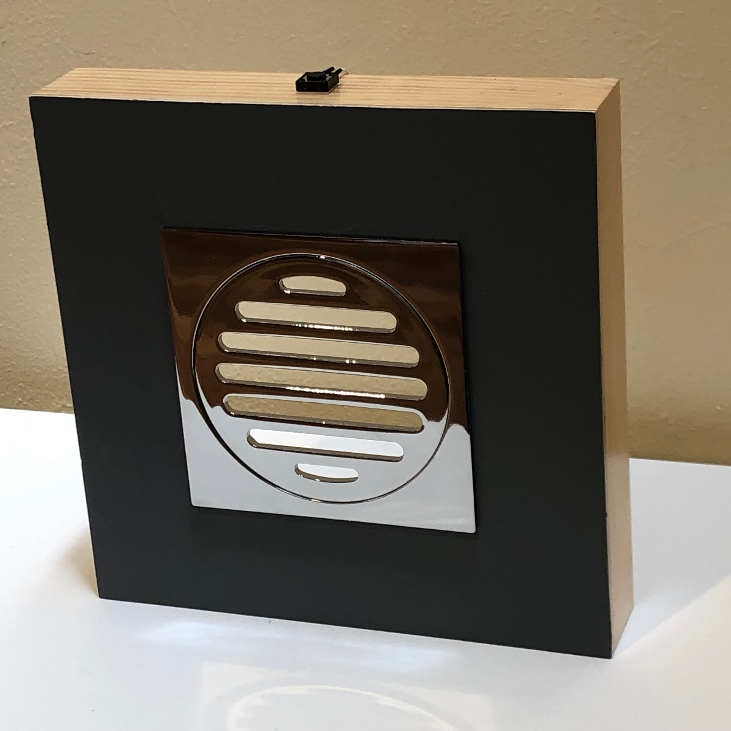 Tom Loveday,  Monochrome 1 , 2018, Acrylic on board and chrome floor vent, recorded sound, 20 x 20 x 3.5 cm, assemblage