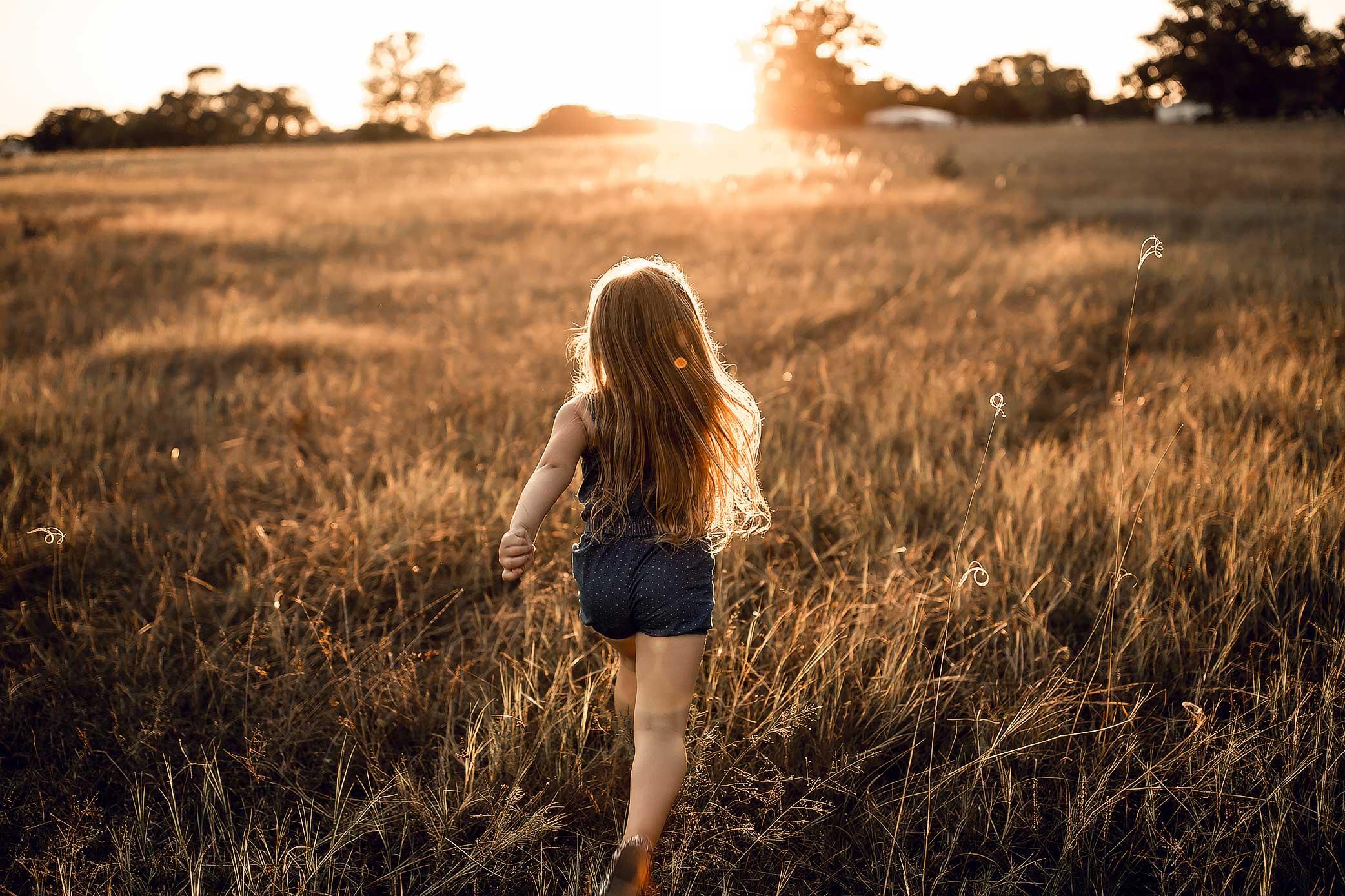 shelby-schiller-photography-child-running-into-the-summer-sunset.jpg