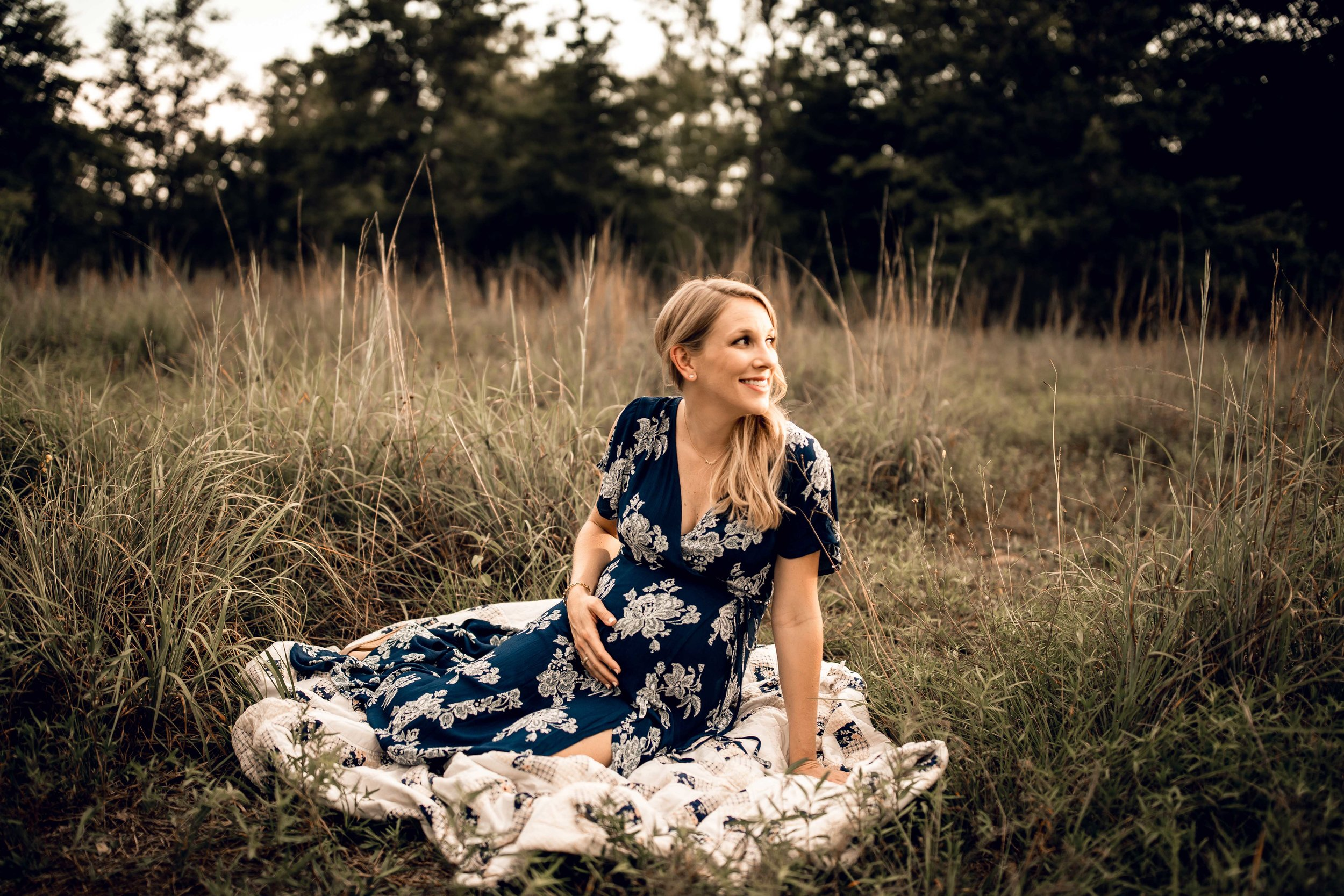 shelby-schiller-photography-maternity-navy-floral-dress-sitting-on-quilt-in-field.jpg