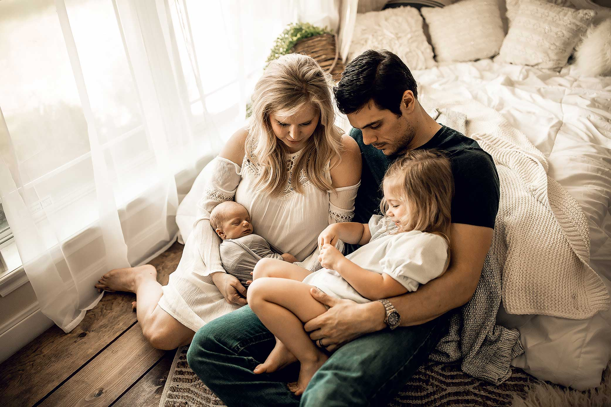 shelby-schiller-photography-lifestyle-newborn-family-curled-up-on-wooden-floor.jpg