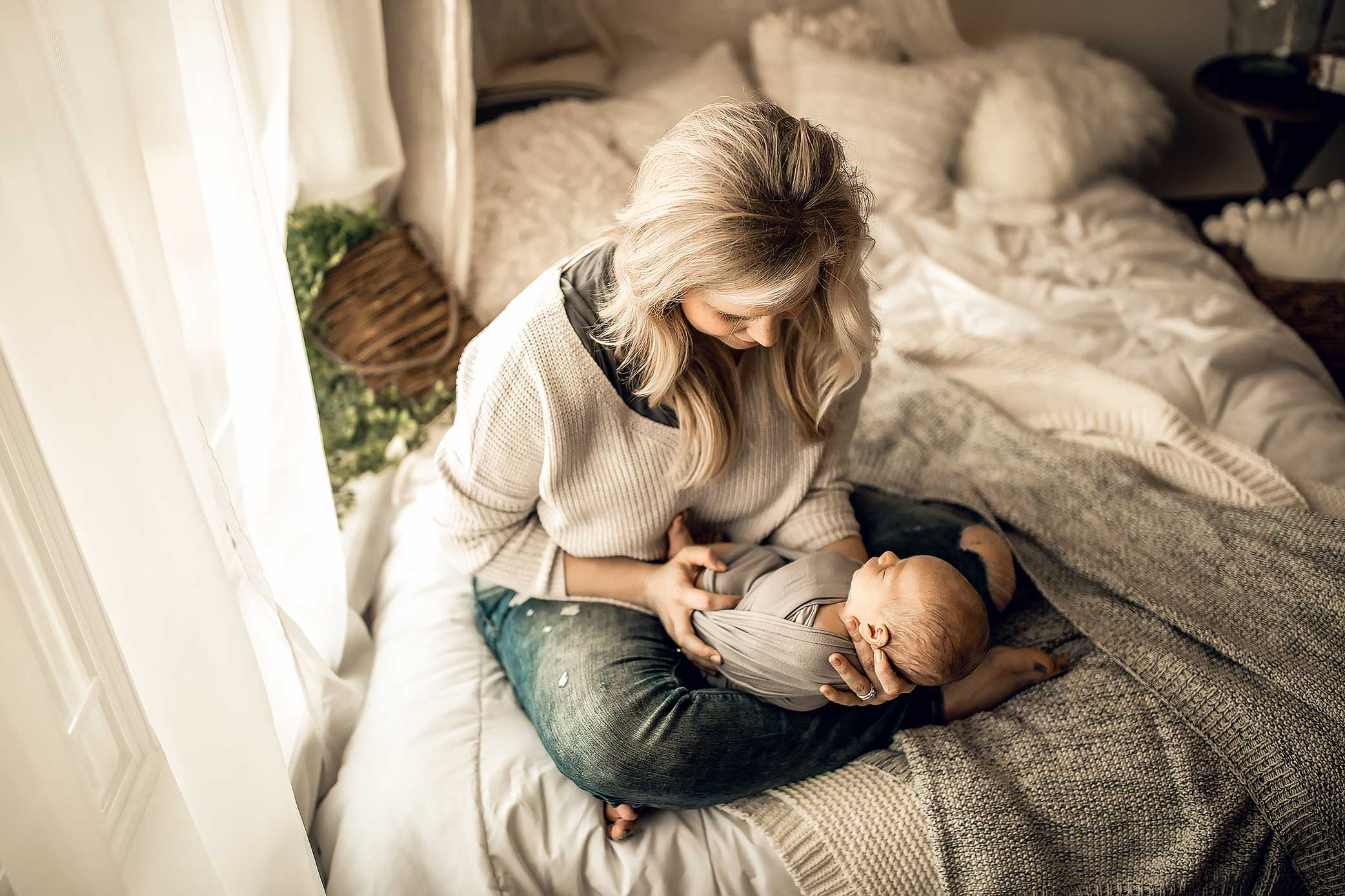 shelby-schiller-photography-lifestyle-newborn-mom-holding-baby-sitting-on-bed.jpg