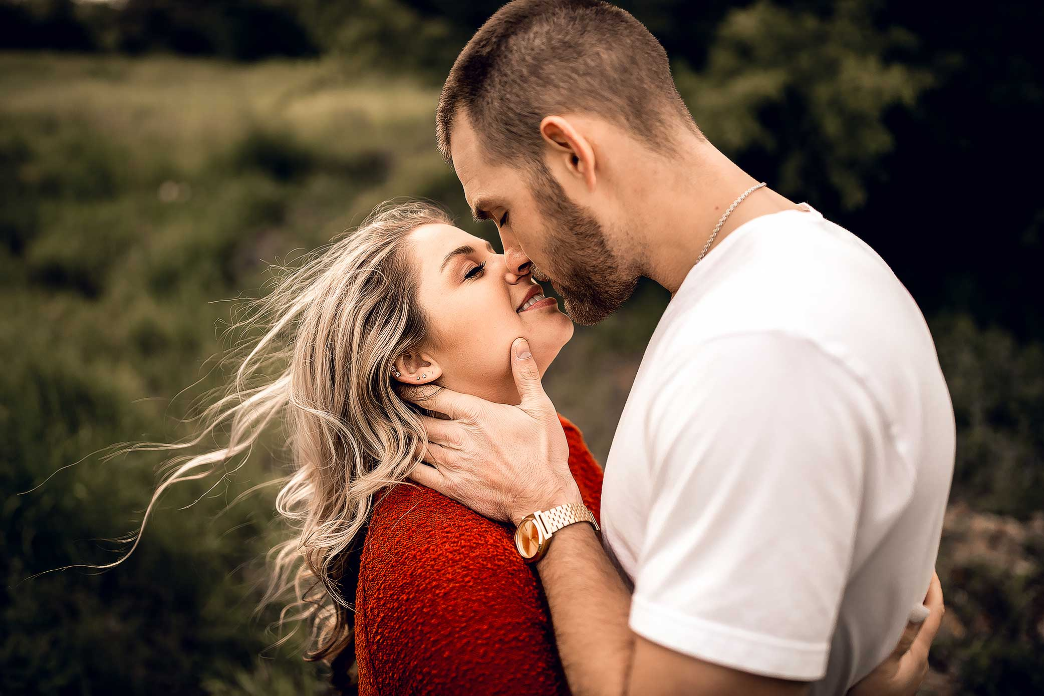 shelby-schiller-photography-lifestyle-couples-cupping-her-face-kissing-hair-blowing-in-wind.jpg