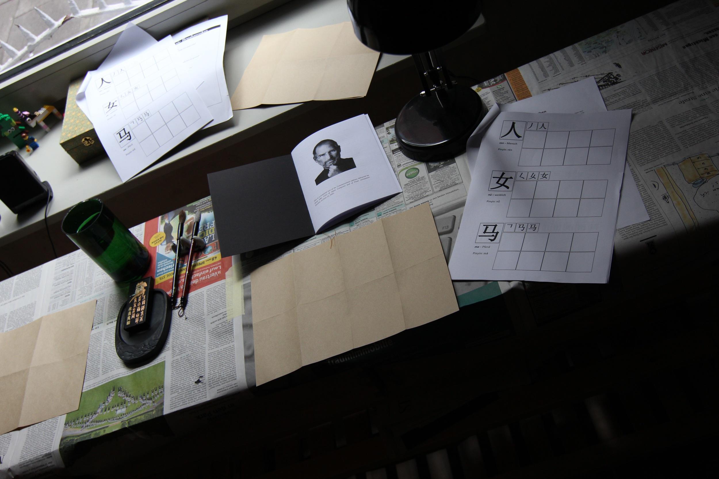 Eine Kalligrafie-Station mit Wasser, Tuschestein, Pinseln, Papier, chinesischen Schriftzeichen als Vorlage und ein Heft mit einer Rede von Steve Jobs, in der er erklärt, warum die Tatsache, dass er das College schmiss dazu führte, dass er Kalligrafie studierte, was wiederum das Design digitaler Devices prägte.