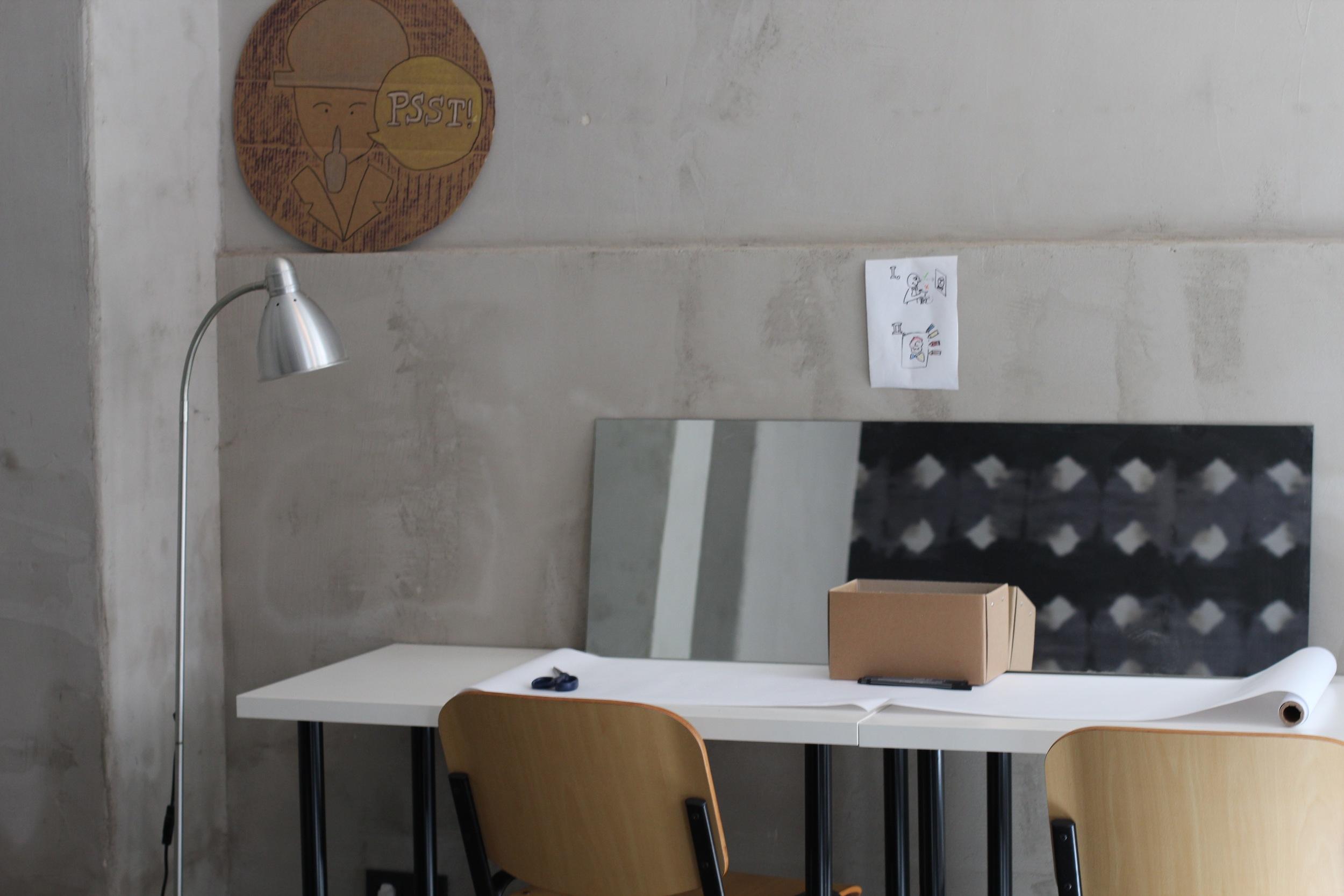 Eine Station mit Spiegel, Papier, dunklen Stiften sowie farbigen Stiften und Kreiden. Eine gezeichneten Bedienungsanleitung erläutert, wie man all dies nutzen kann, um ein Selbstportrait zu erstellen.