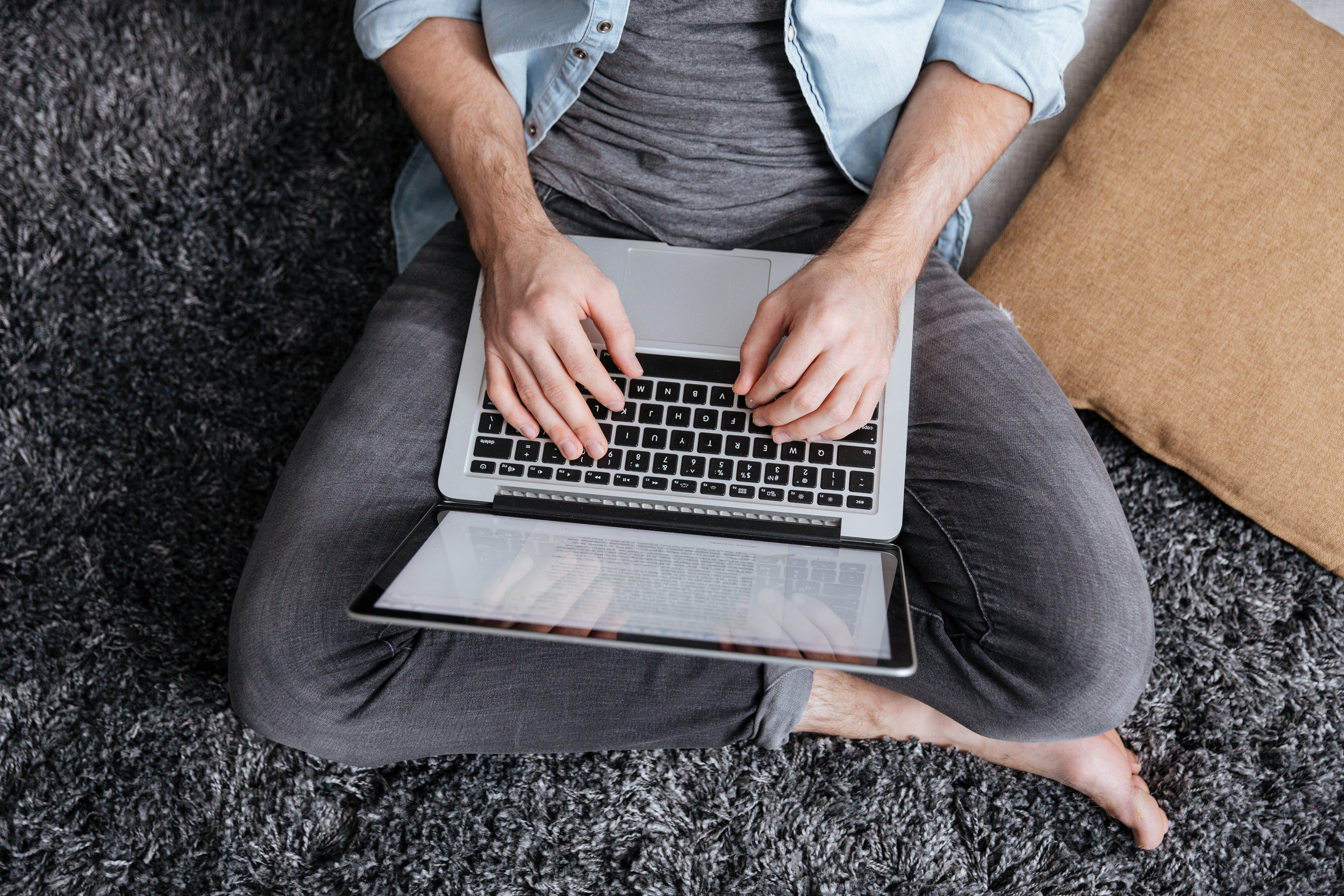 graphicstock-top-view-of-a-casual-man-sitting-on-carpet-and-typing-on-laptop-computer-at-home_BduhP3Inl.jpg