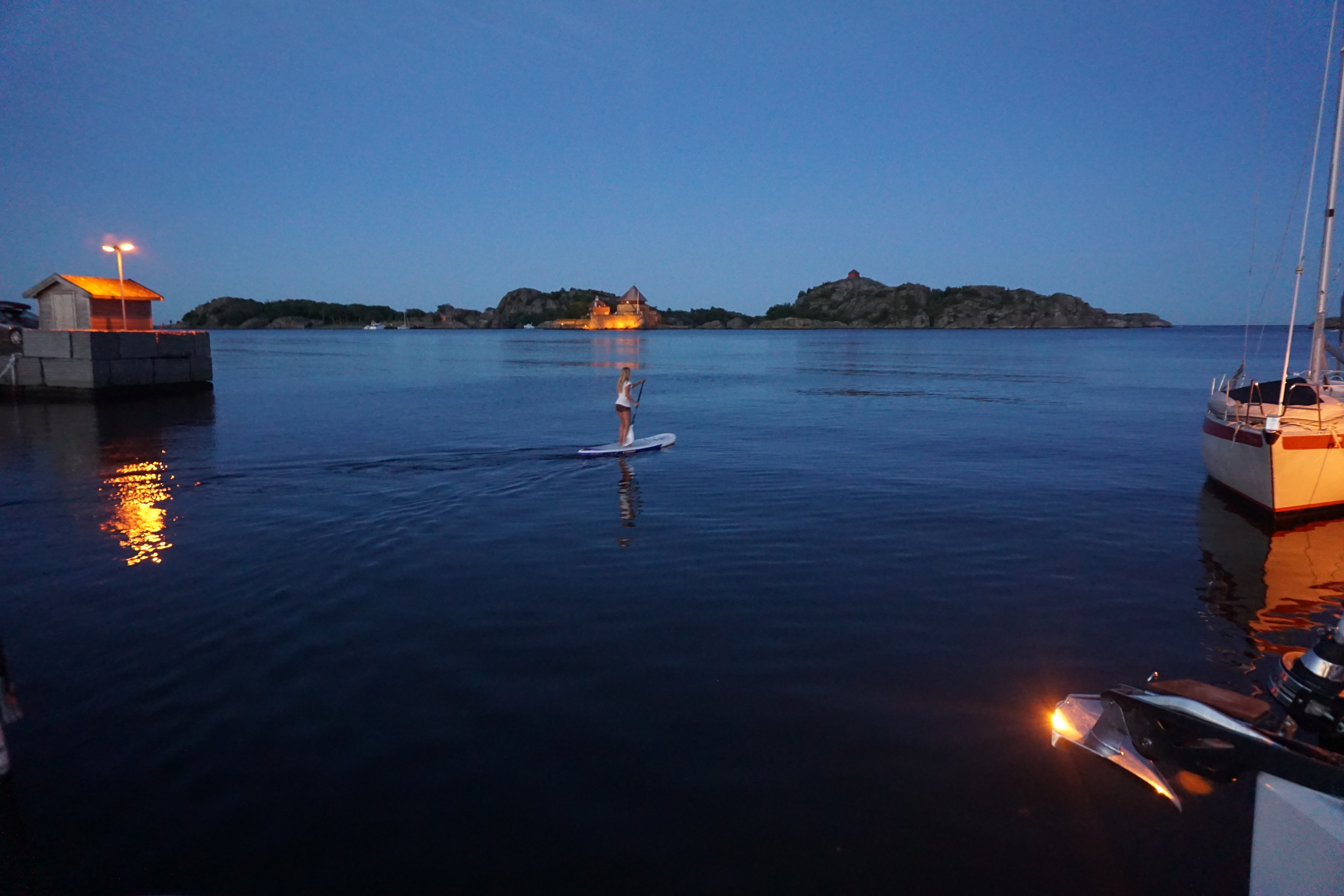practicing Stand-up paddling in stavern by night.