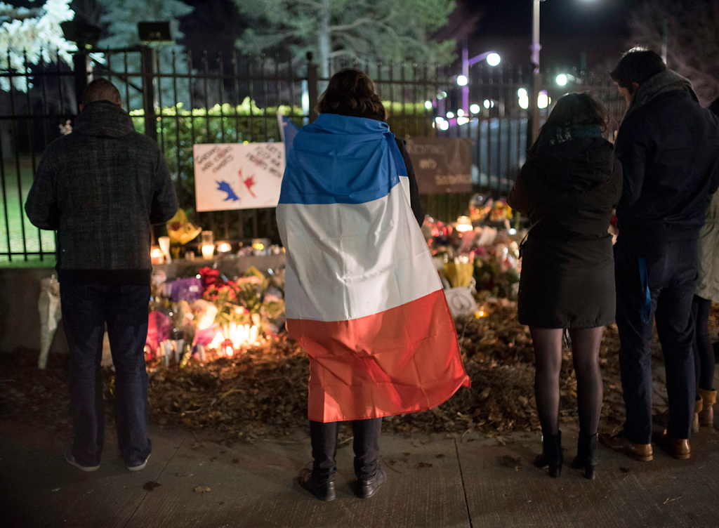 A person wears a French flag at a memorial outside the French Embassy, Saturday, Nov. 14, 2015, in Ottawa, Ontario, following deadly attacks in Paris on Friday.   Photo by Justin Tang/The Canadian Press via AP