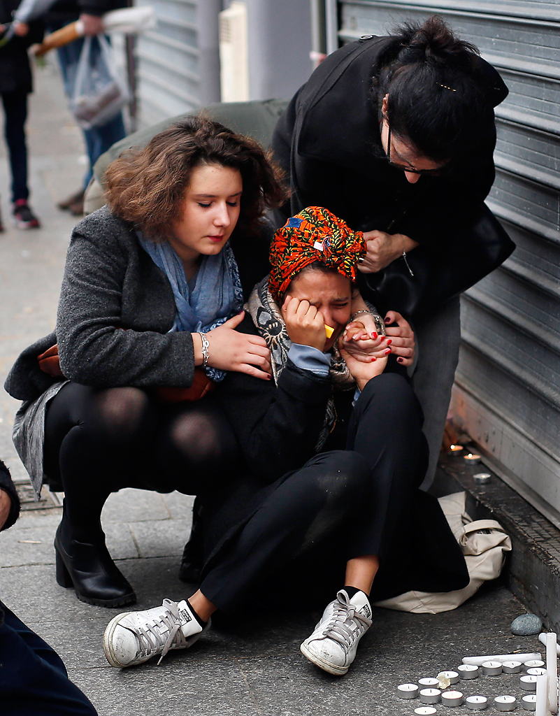 A woman is comforted by others outside the Carillon cafe and the Petit Cambodge restaurant in Paris, Saturday Nov. 14, 2015, a day after over 120 people were killed in a series of attacks in Paris.  Photo by Jerome Delay/AP