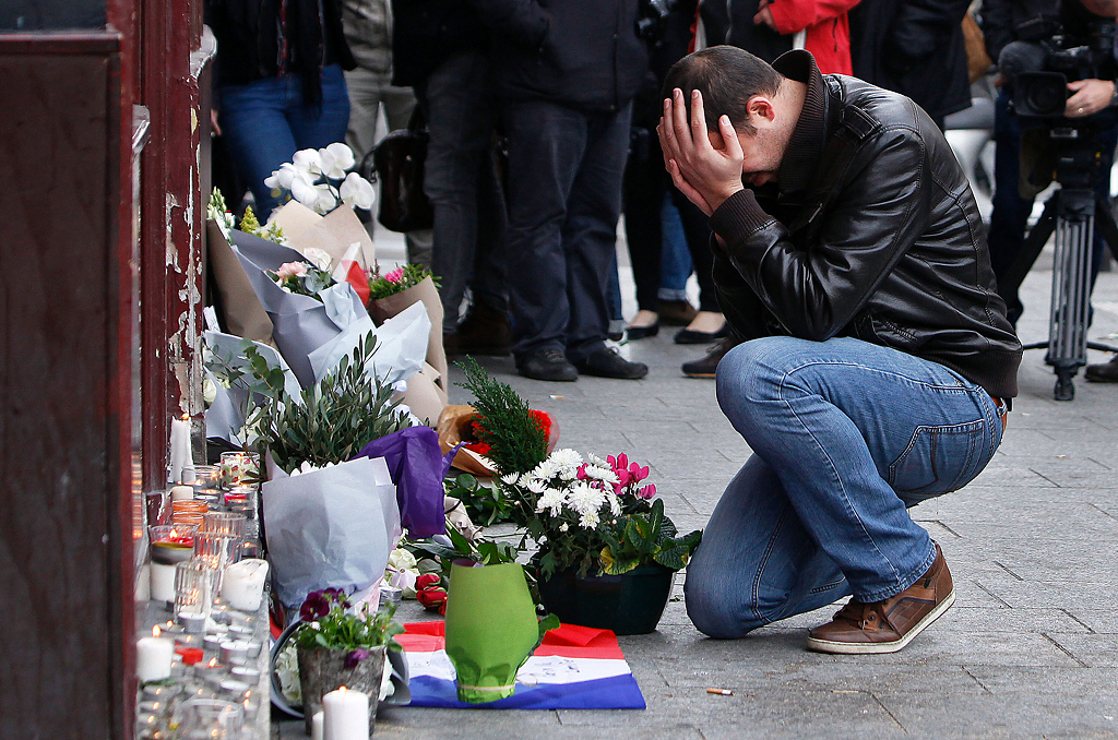 A man holds his head in his hands as he lays flowers in front of the Carillon cafe, in Paris, Saturday, Nov.14, 2015. French President Francois Hollande vowed to attack Islamic State without mercy as the jihadist group admitted responsibility Saturday for orchestrating the deadliest attacks inflicted on France since World War II.  Photo by Thibault Camus/AP
