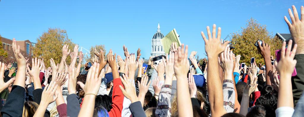 "Concerned Student 1950 supporters throw their hands up to block media from taking photos on Monday, Nov. 9, 2015. The media was unwelcome inside the circle of supporters and were yelling, ""get the media out!""  Photo by Halee Rock/Missourian"