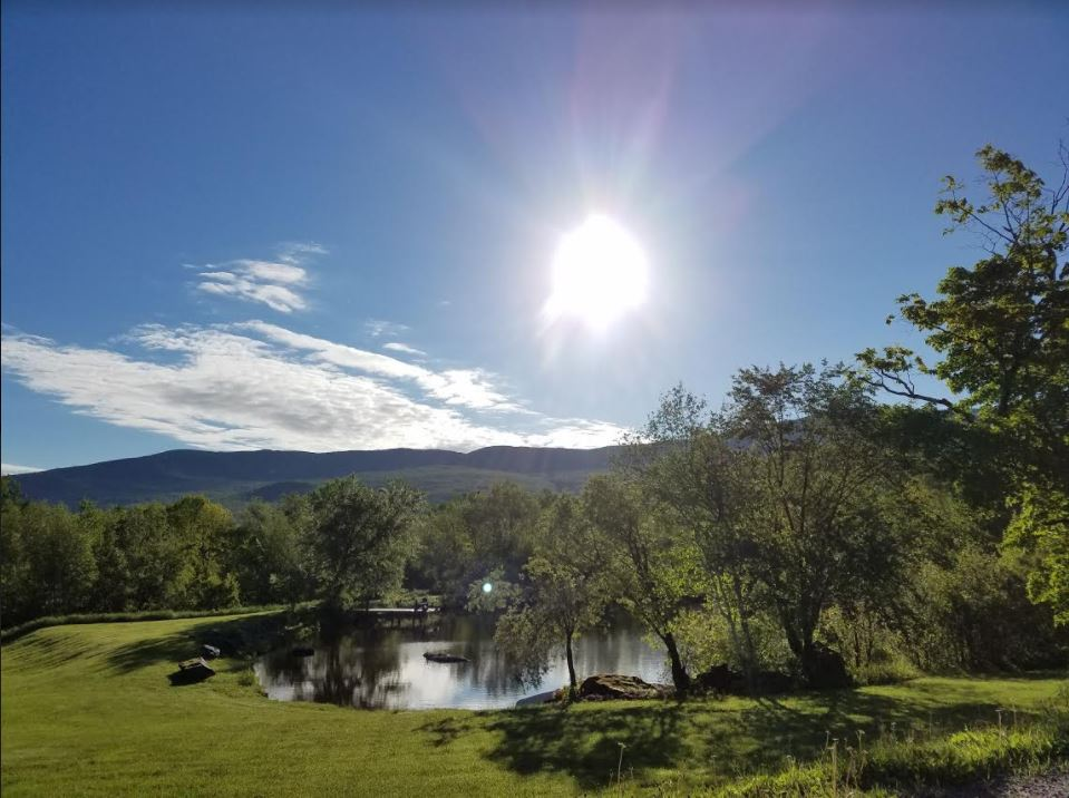 Sunny view of the pond from the front porch of our Vermont Bed and Breakfast