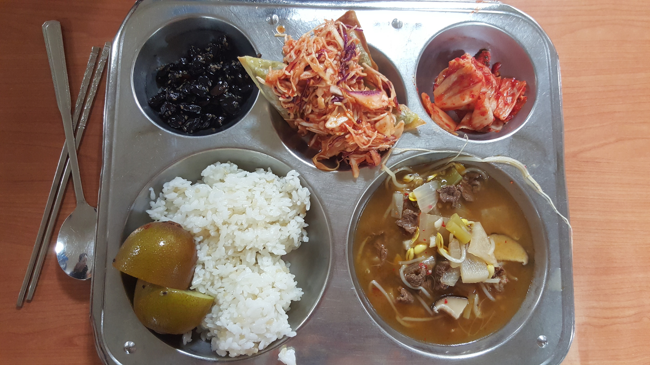 Dumplings with cabbage salad, soup with beef, rice, black beans, kimchi & kiwi