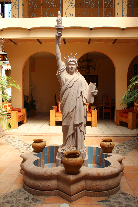 A courtyard in a Mexican house, with a Statue of Liberty adorning the fountain.
