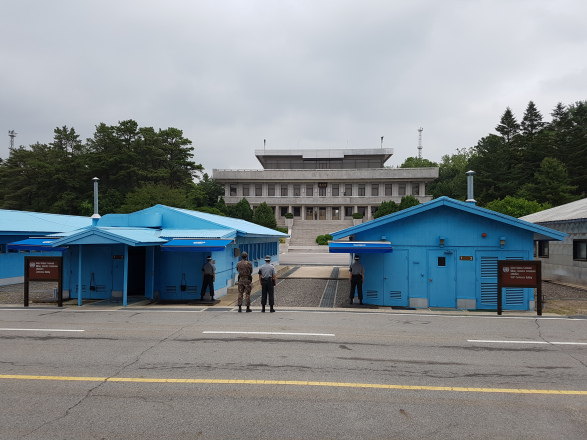 The JSA tour group was allowed to take a photo here, at the site of the 38th parallel, where South Korean guards stand at attention all day, half behind the blue conference houses and half exposed to the North Korean side, in case an attack occurs. The building on the opposite side belongs to North Korea. The man standing on the steps of the building is a North Korean solider and, allegedly, behind those windows are plenty other soldiers watching us take photos of them.