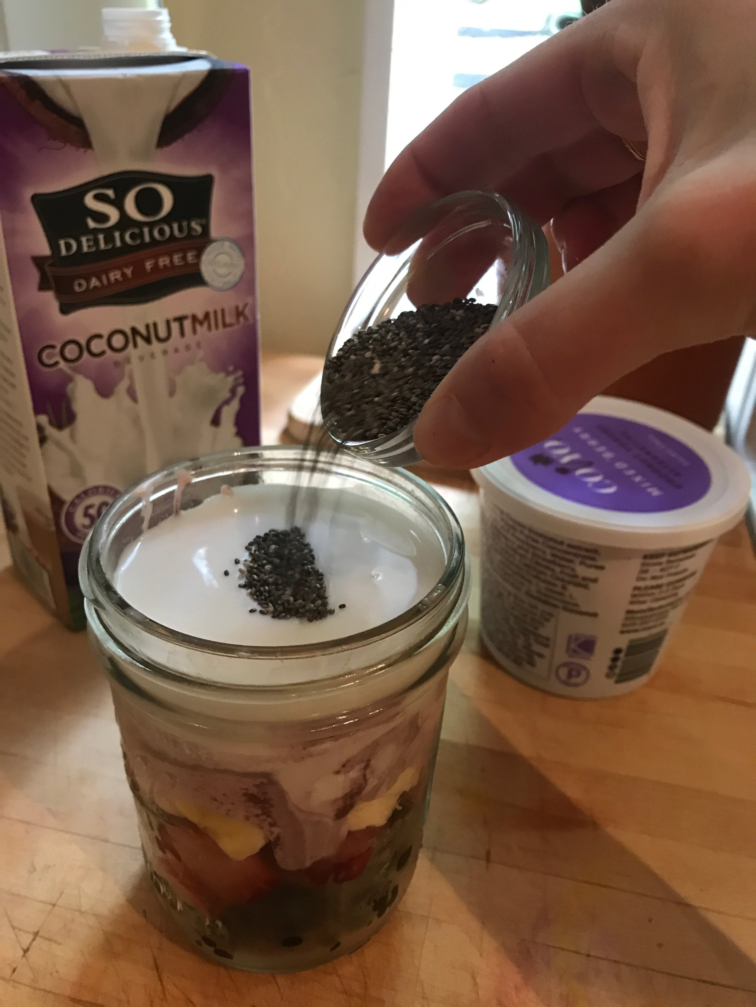 Adding the top layer of chia seeds before gently stirring with the coconut milk.
