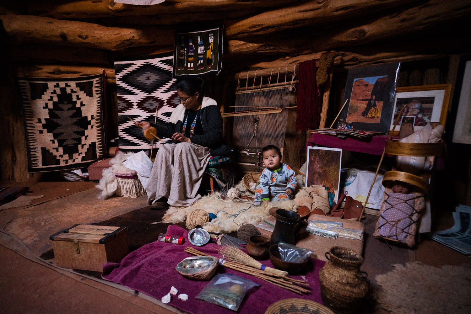 Inside the hogan, a woman works on traditional crafts while her child chills out on what looked like a comfy sheep skin.