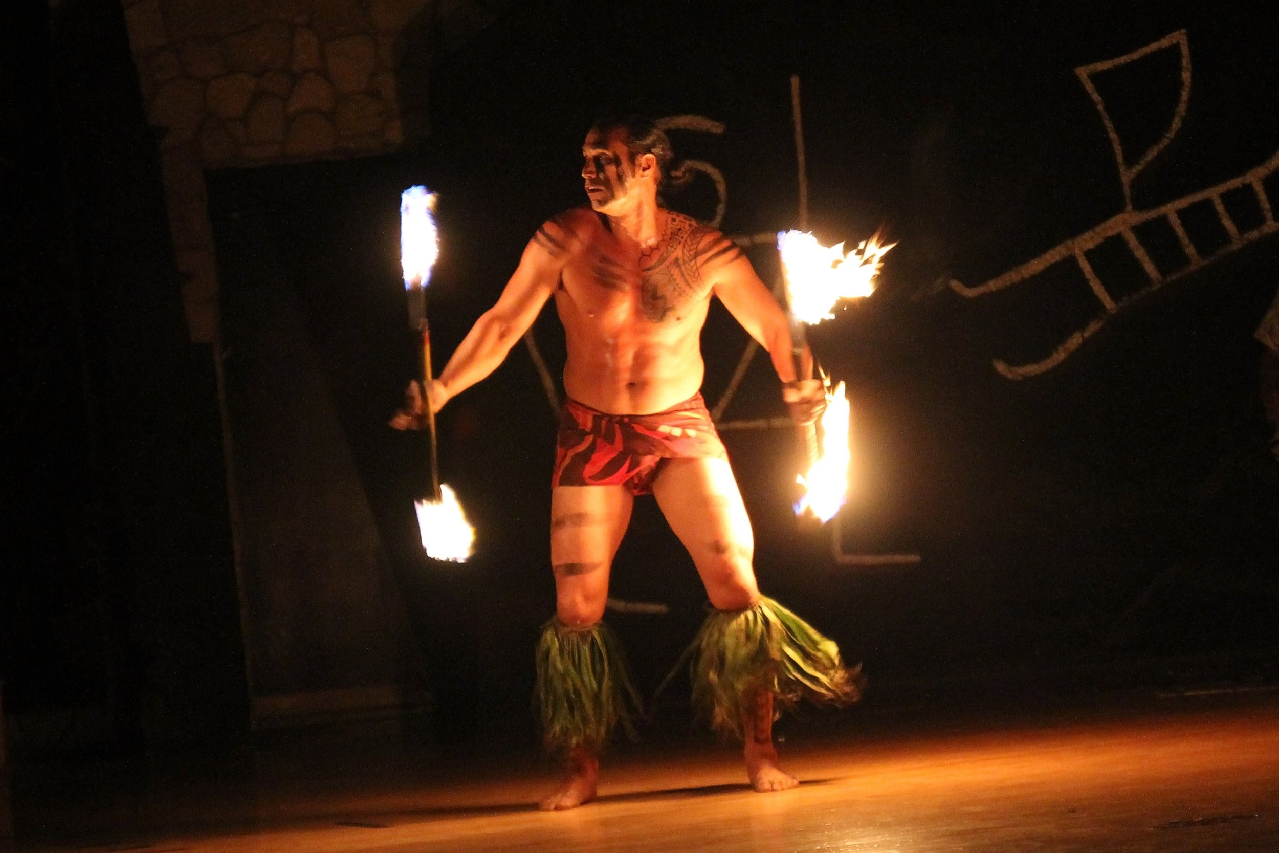 A Hawaiian man performing a fire dance with torches