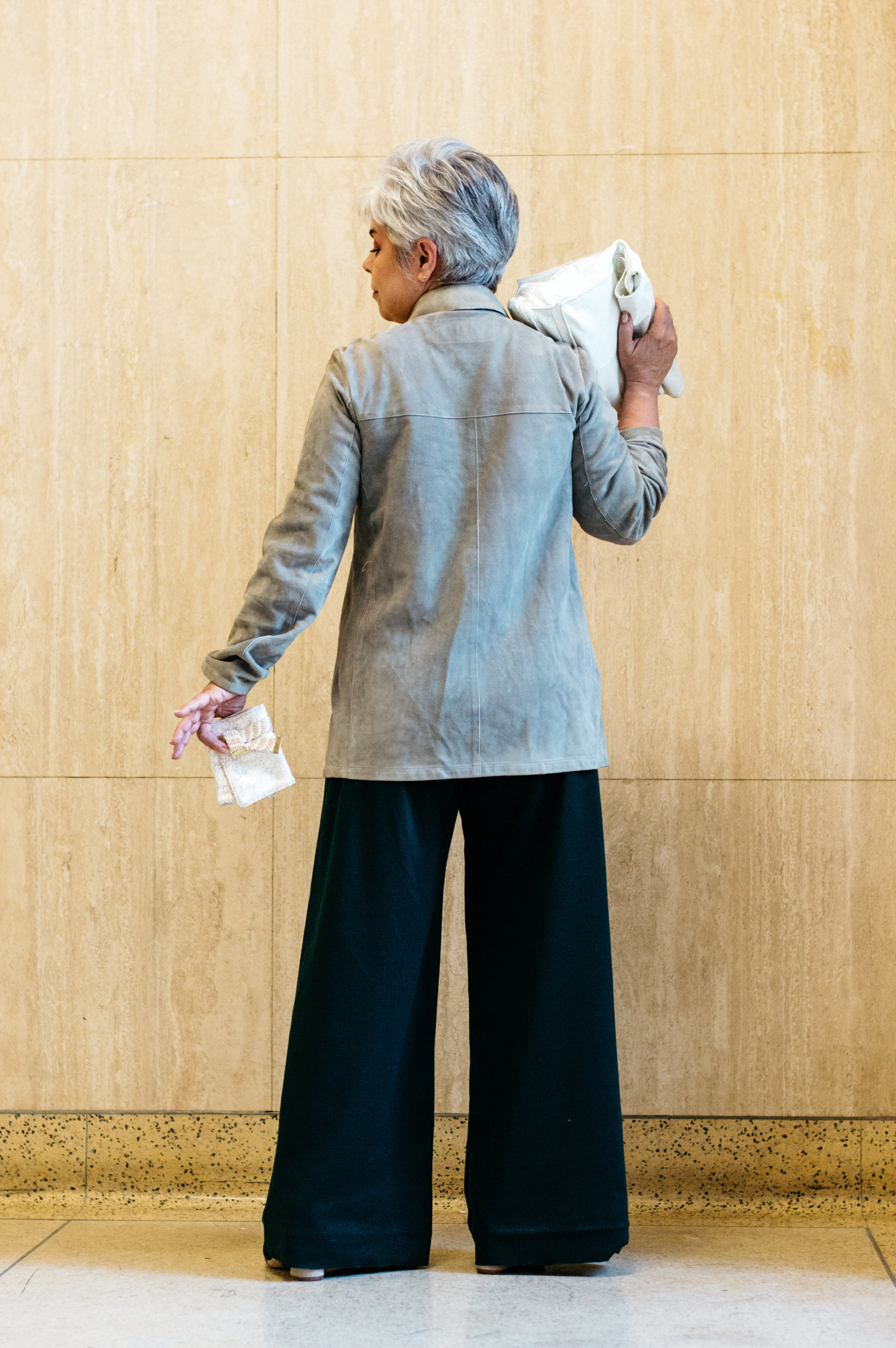 Linda models the Five Fold clutch and Triptych wallet, and Moss trousers by EVA.      Shirt: Designer's own.