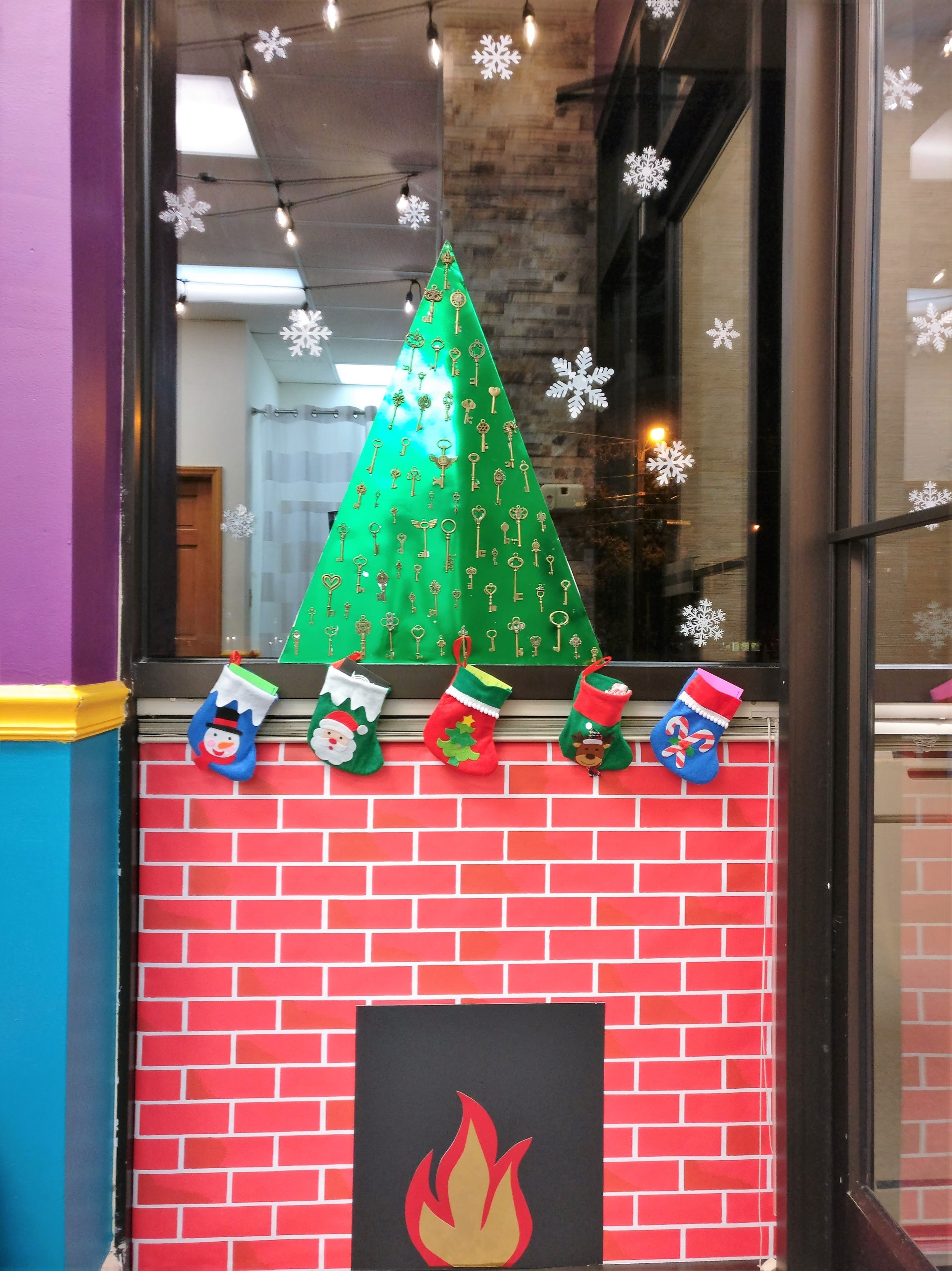Bull City Escape's window display. The tree is hung with keys and the stockings are filled with riddles, stickers, and candy.