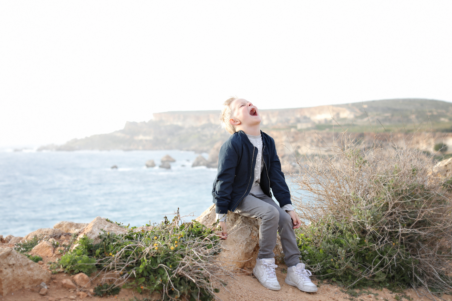 golden bay malta, cliffs, natural light photographer, laughter, whimsical, kids photography, bomber jacket, swedish photographer malta