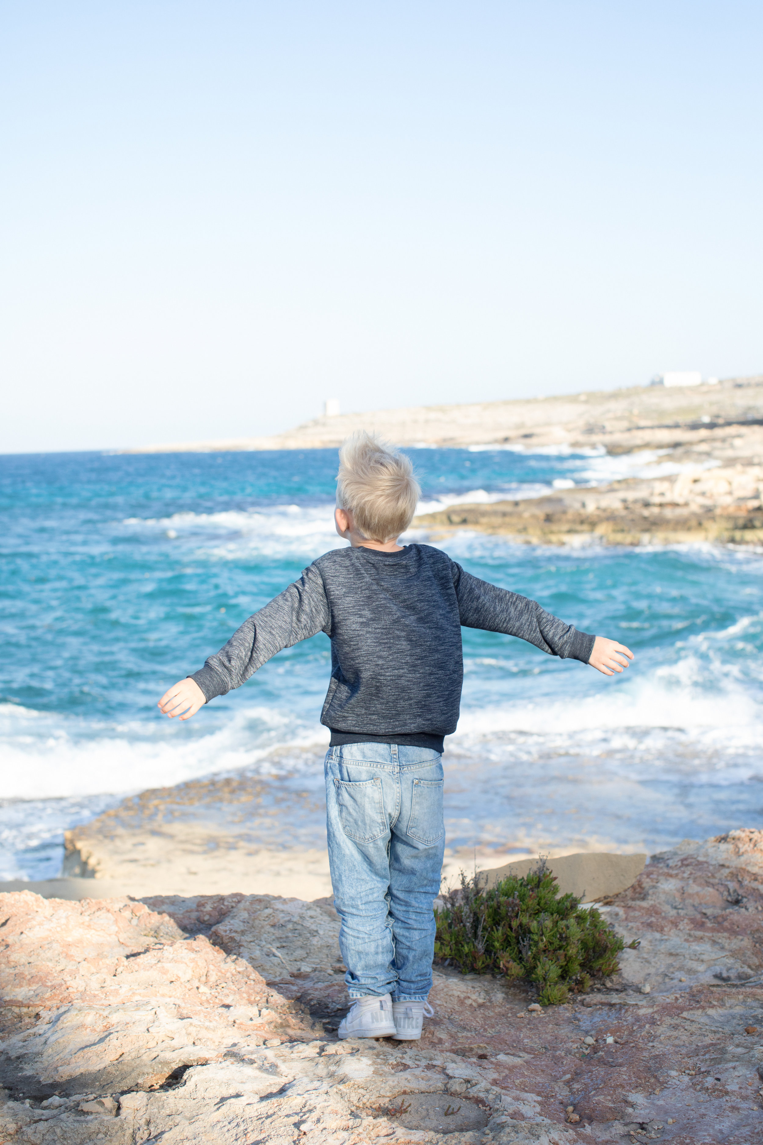 bahar-ic caghaq, mediterranean sea, children photographer malta, stormy sea, windy, whimsical happy child, cliffs, playing, childhood