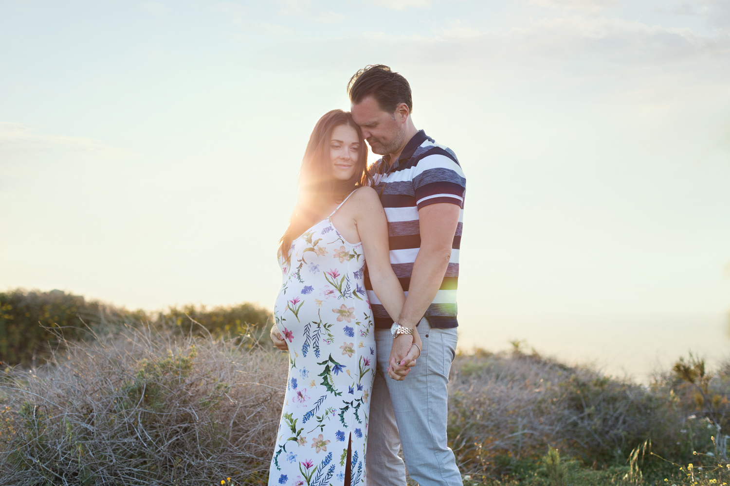riviera bay couple in love maternity dress holding hands sunset maternity shoot malta expecting parents