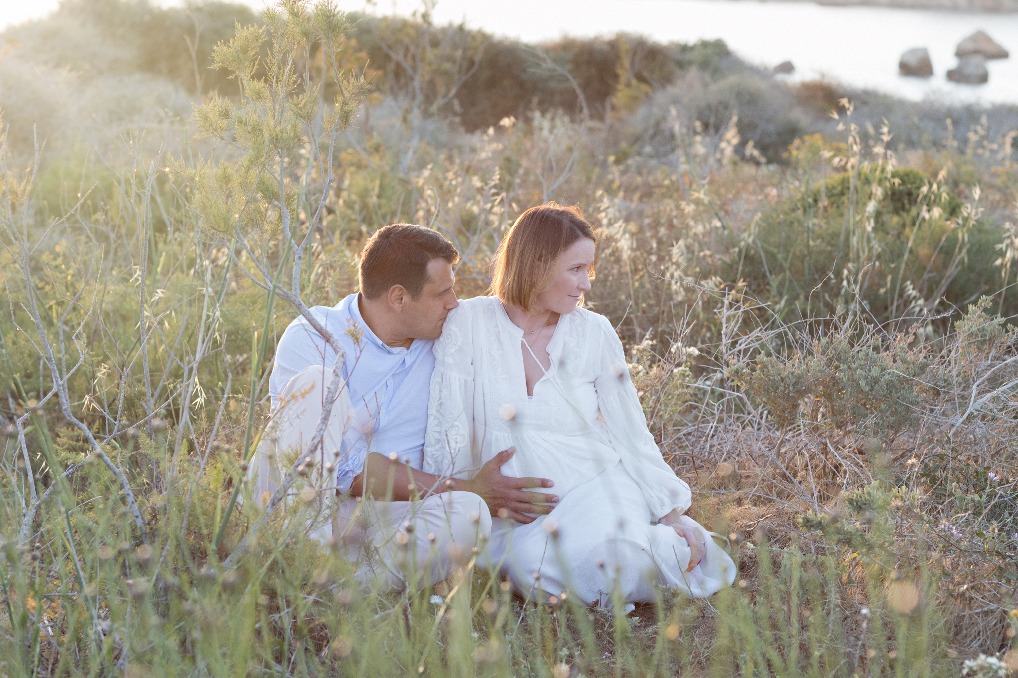 cuddling parents, parents to be, first baby, mountains of riviera bay, high grass, sunsetting, backlight, maternity photo shoot malta