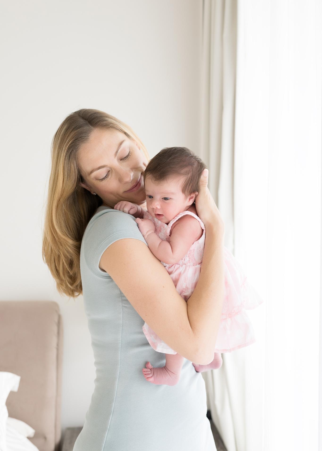 mother holding her newborn baby girl- window light-stylish mama-in home newborn photoshoot