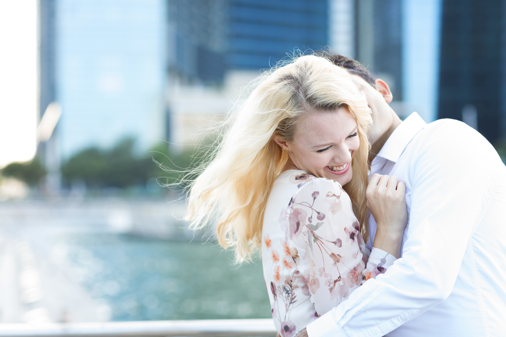 laughing couple at marina bay sands engagement photoshoot in natural light with backlight gorgeous couple smiling and kissing