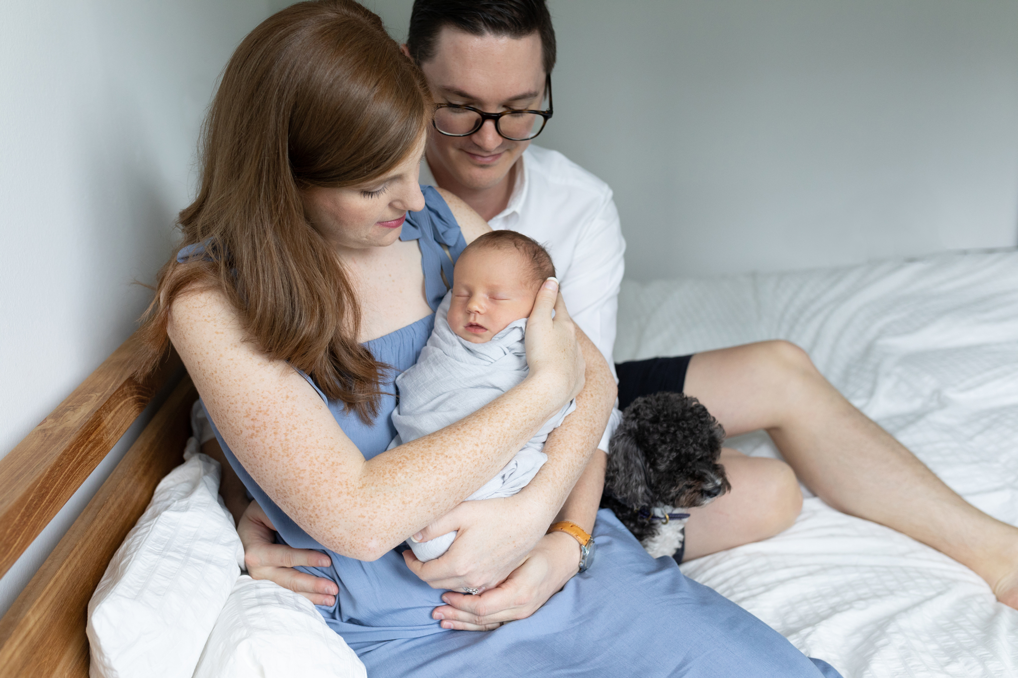 mother and father sitting in bed cuddling their newborn son and their dog is in bed too gorgeous newborn session in singapore