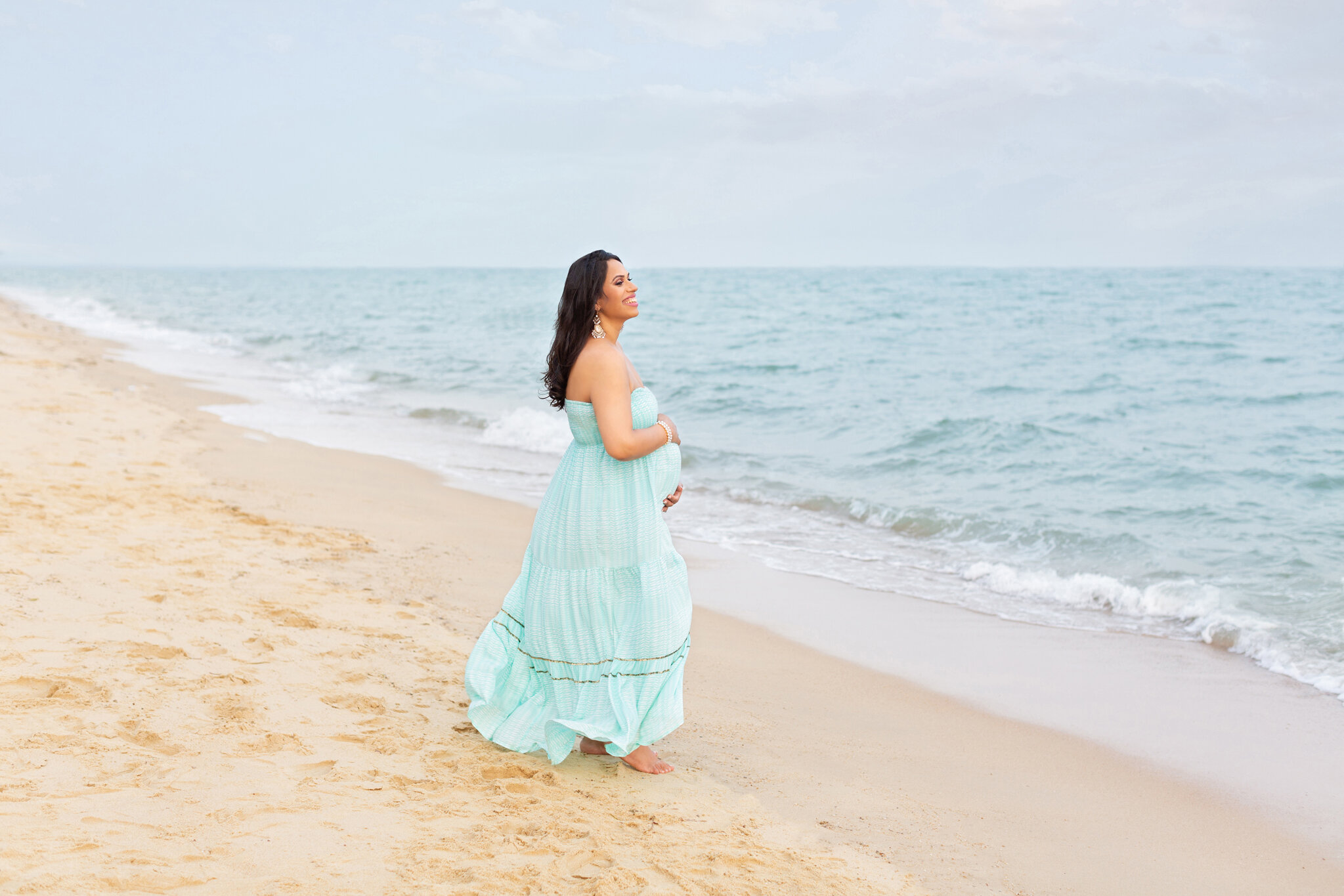 gorgeous outdoor maternity session on east coast beach singapore on a windy afternoon, maternity dress is stunning and woman is laughing and we capture lovely photographs of her growing belly
