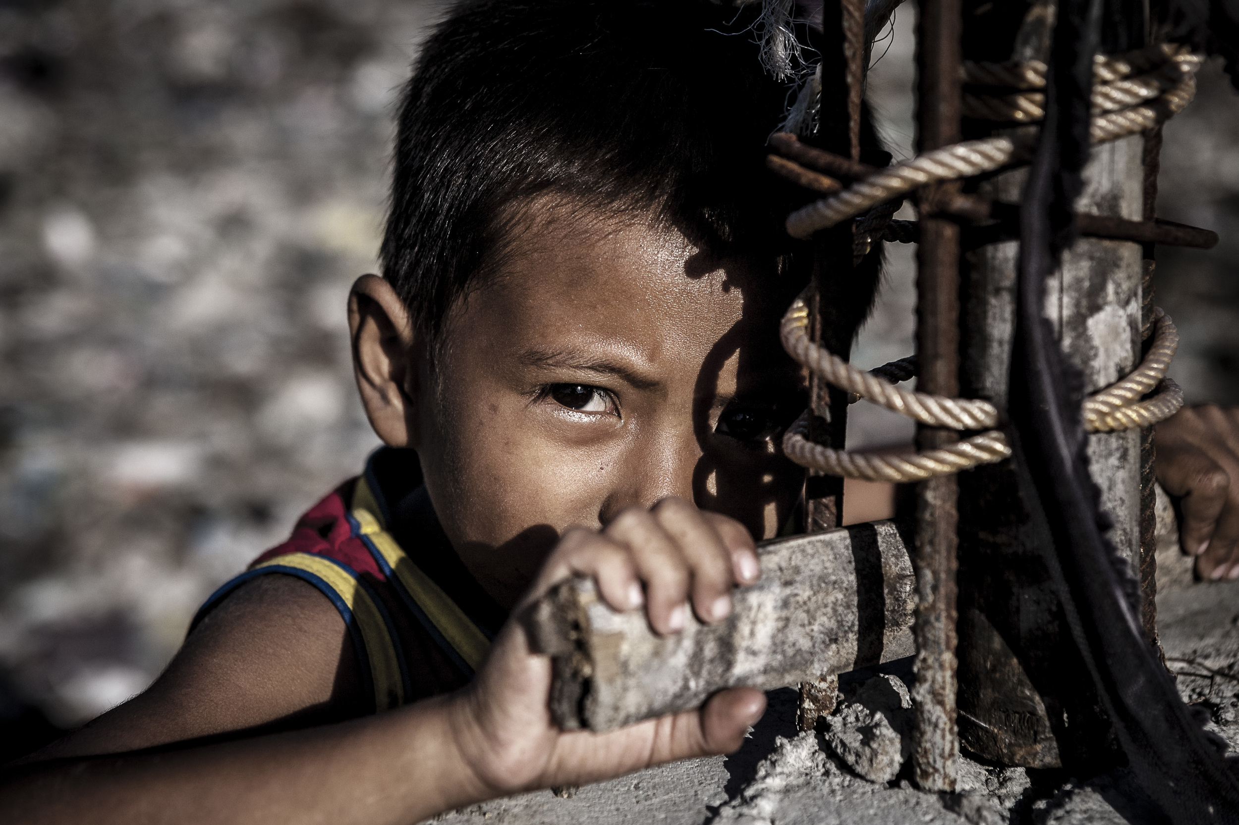 Poverty: small boy living on Sawung tip in Bali Indonesia. He ran away before I could ask his name.