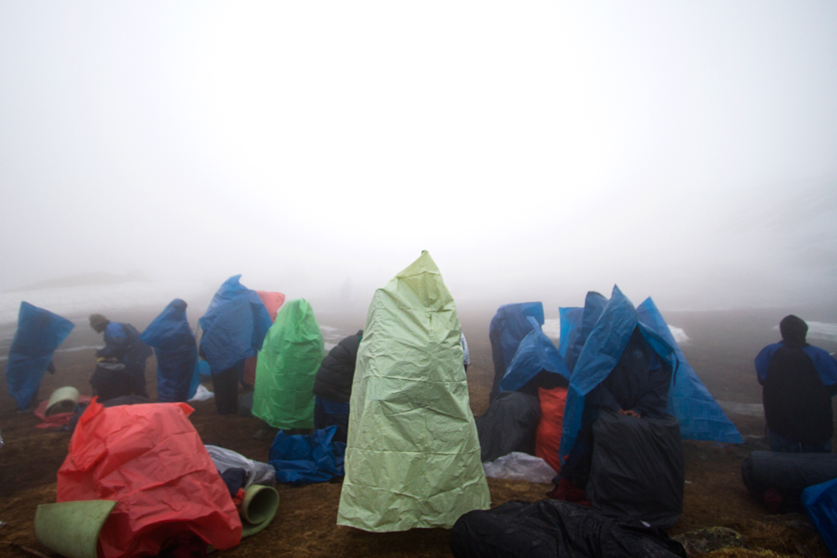 Students sheilding themselves from the rain at the advance base camp after descending from camp 1.