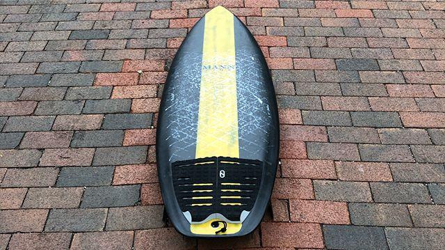 """I've never had a #MannKine board I didn't absolutely love, and this one is no exception! 5'4"""" carbon fiber toy by @dan__mann with a yellow resin racing stripe for an extra bit of speed. 🖤💛🖤 I grabbed this one from Dan shortly after landing in California for this year's @boardroomshow in what has become a yearly tradition of grabbing my first board of the trip from him. Each year Dan completely knocks the skin off the ball with the sled he hands off. This one might be the best one yet. It takes the best elements of the Potato line and Spitfire Dan released with @firewiresurfboards and blends them with his very unique (and for the moment top secret) bottom contours he's been throwing on many of his customs over the past couple years. The result is a highly functional performance groveler that works well in most conditions. I'm really hoping to see this one become widely available through @firewiresurfboards but it's always available via a custom from the Mann himself. Thanks again, @dan__mann for giving me so many good sessions! 🙌🏼🙌🏼 Thanks again, @surf_n_show and fam for the #kookselfie vids! 🙌🏼🙌🏼 #danmann #mannkine #carbonfiber #quad #surfboard #ronsquiver"""