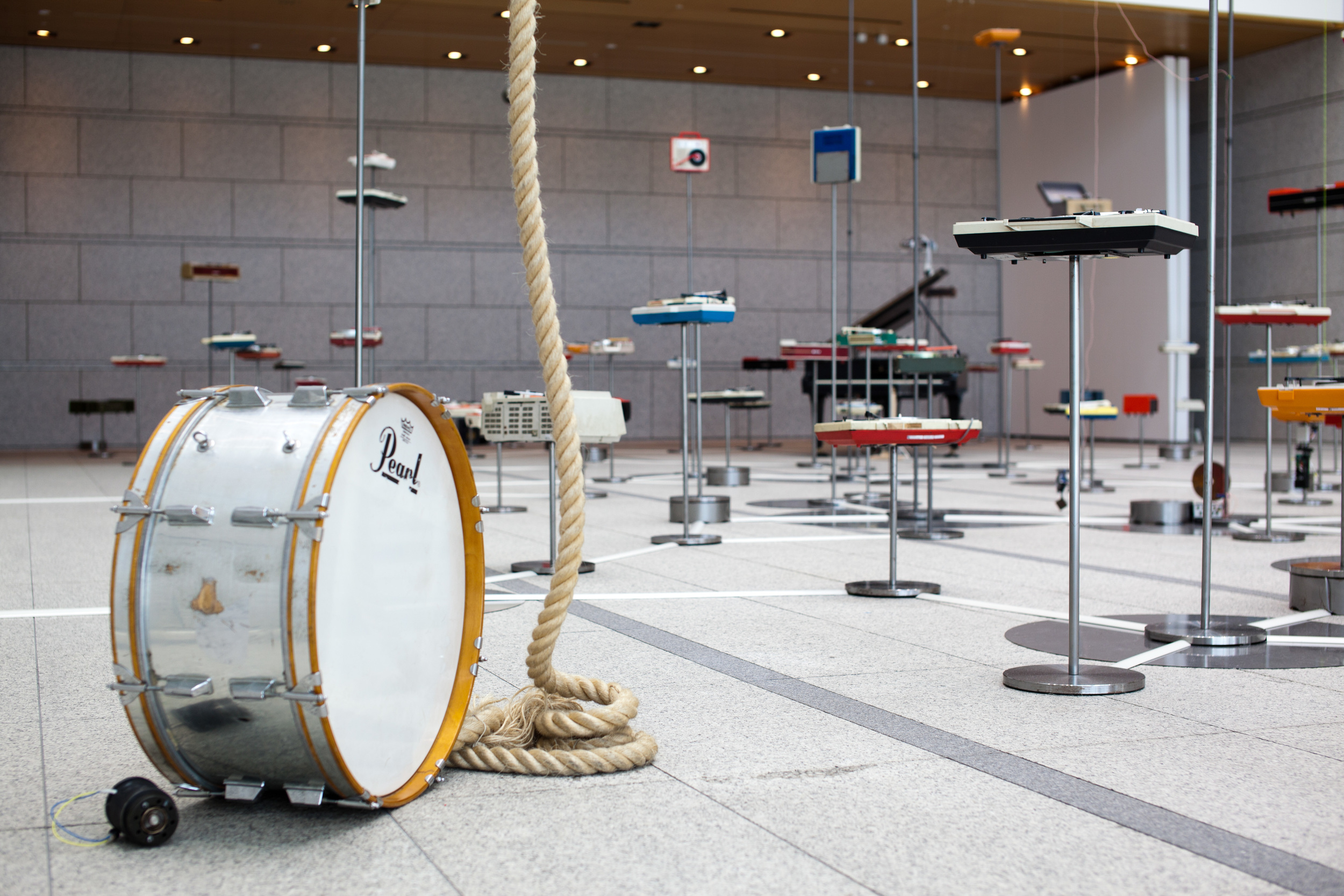 Yuko Mohri   with without records,  2012 Installation View at Museum of Contemporary Art, Tokyo, Japan, 2012 bass drum, rope, motor, grand piano, censor, doll, etc. dimensions variable